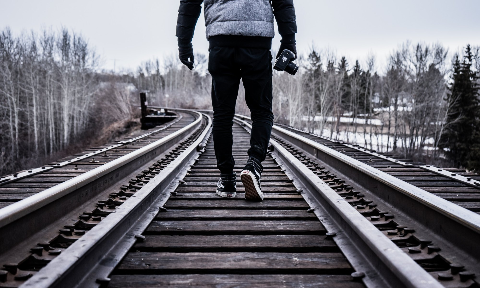 A courageous man holding a camera walking on a train track during winter