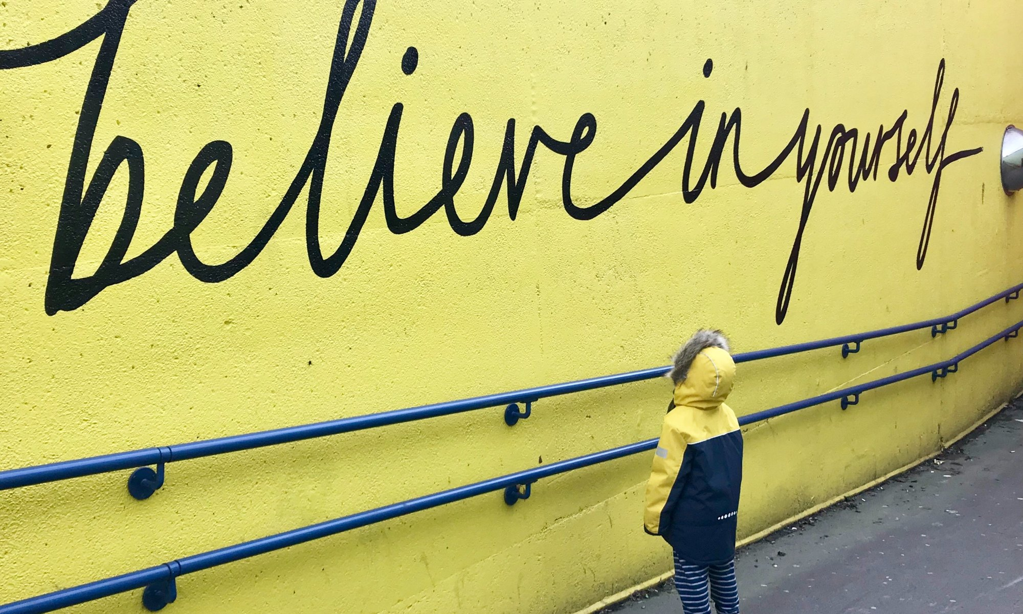 "A boy looking at a yellow wall that says ""believe in yourself"""