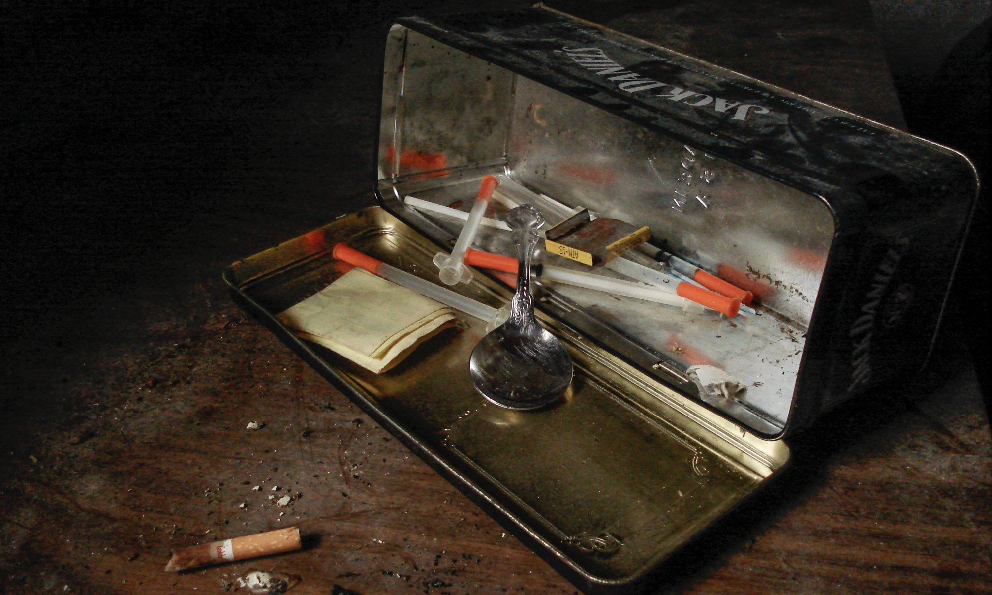 An open container with needles, drugs, spoons and cigarettes