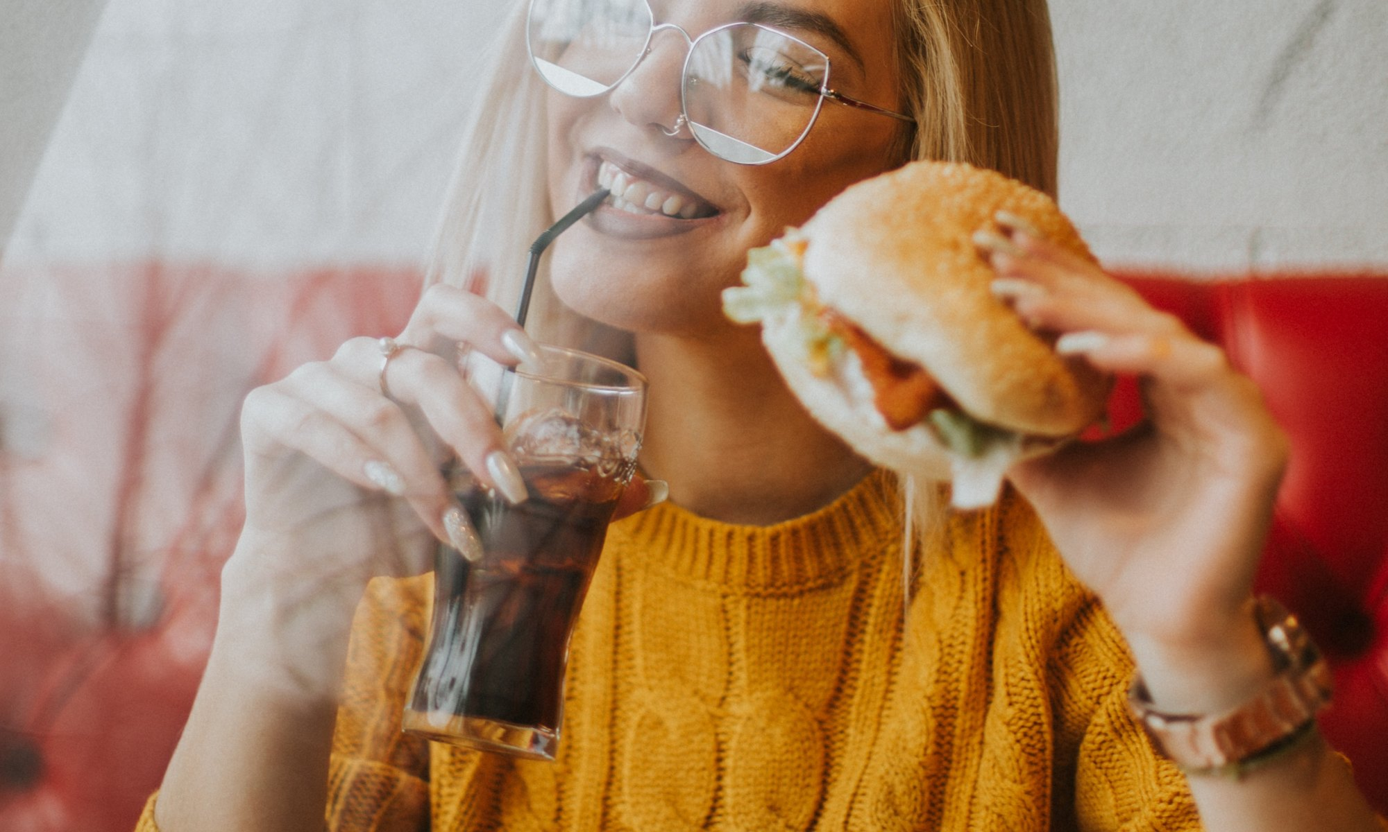 Blonde woman smiling and eating a burger and fries and drinking coke