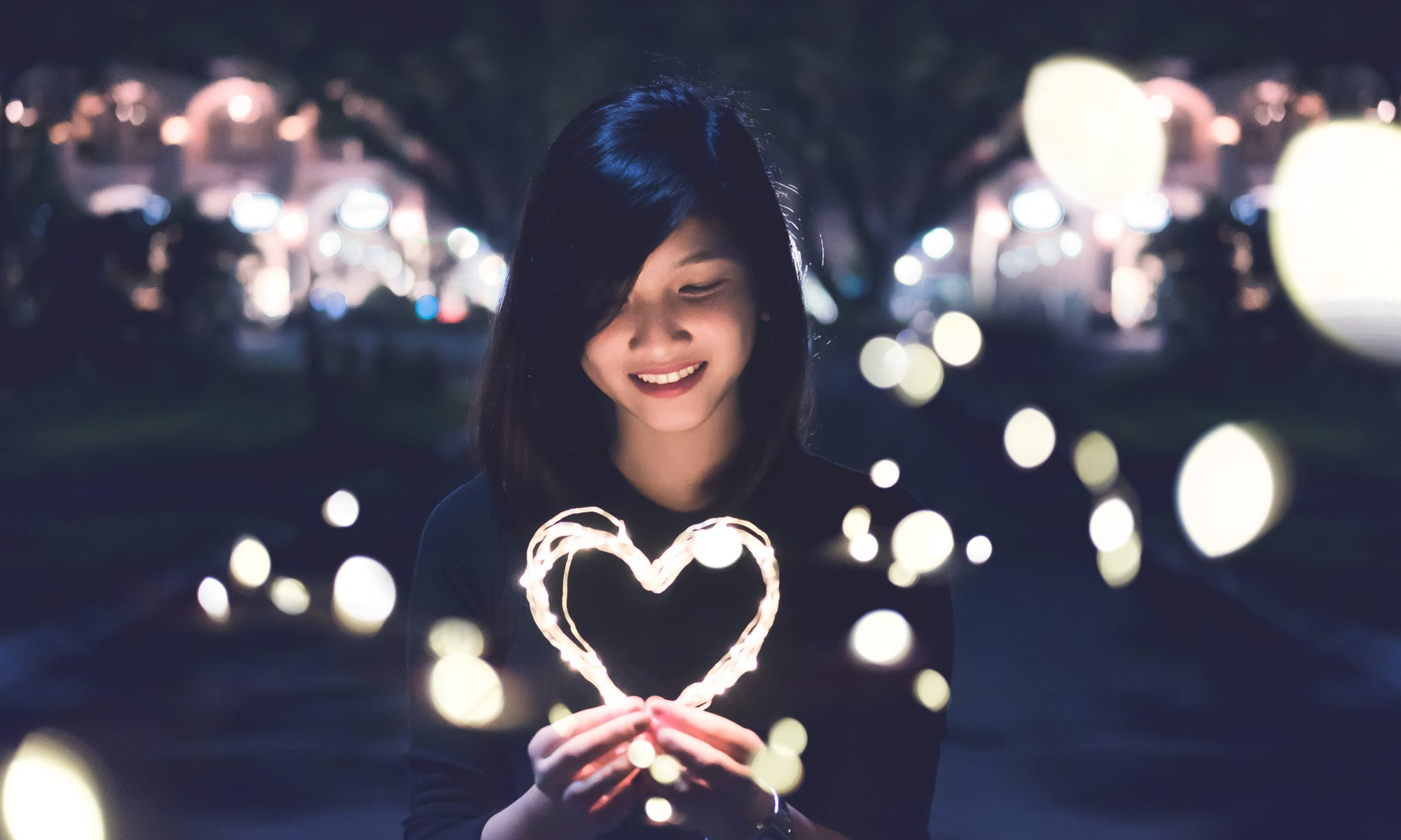 Asian woman following her intuition and holding lit heart