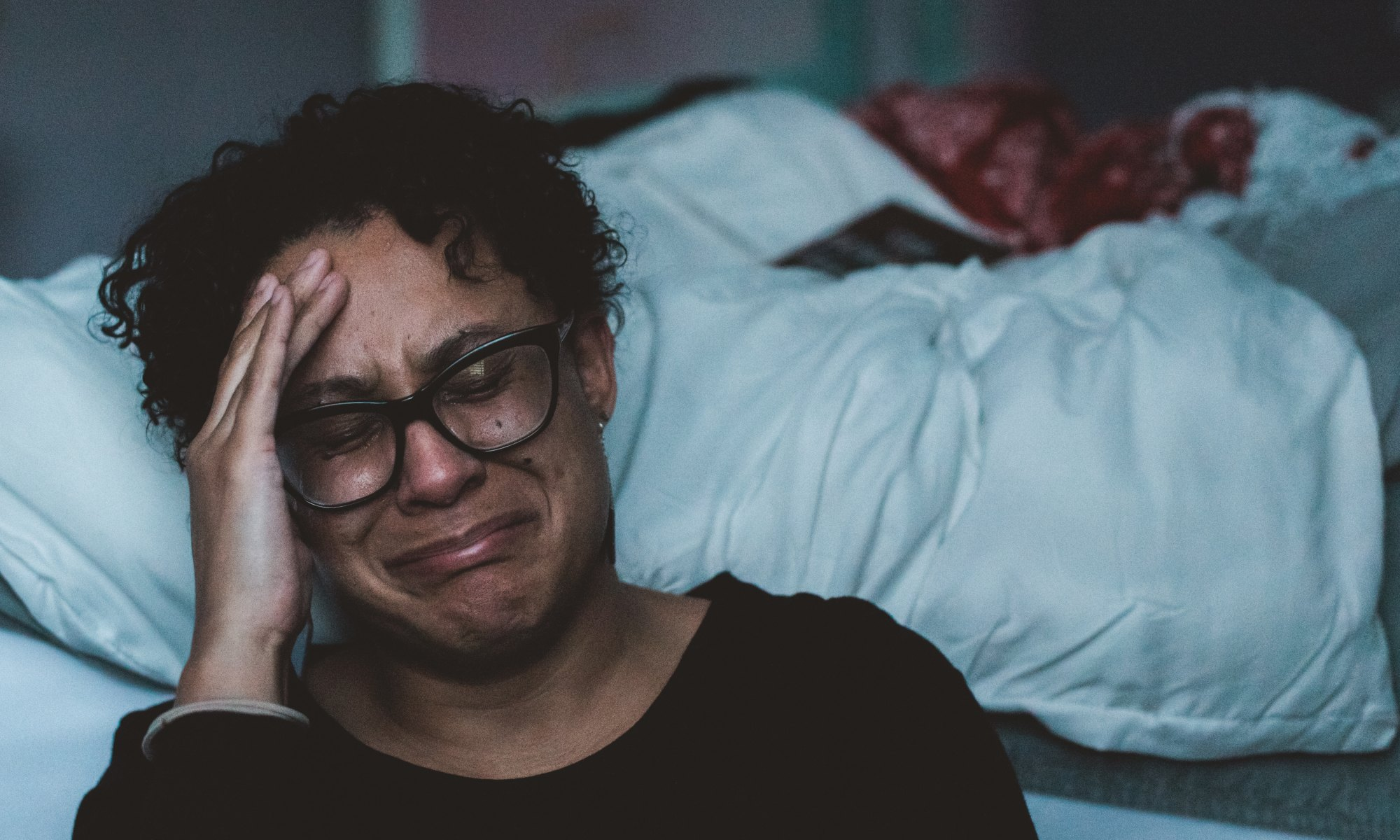 Depressed African American female crying beside bed