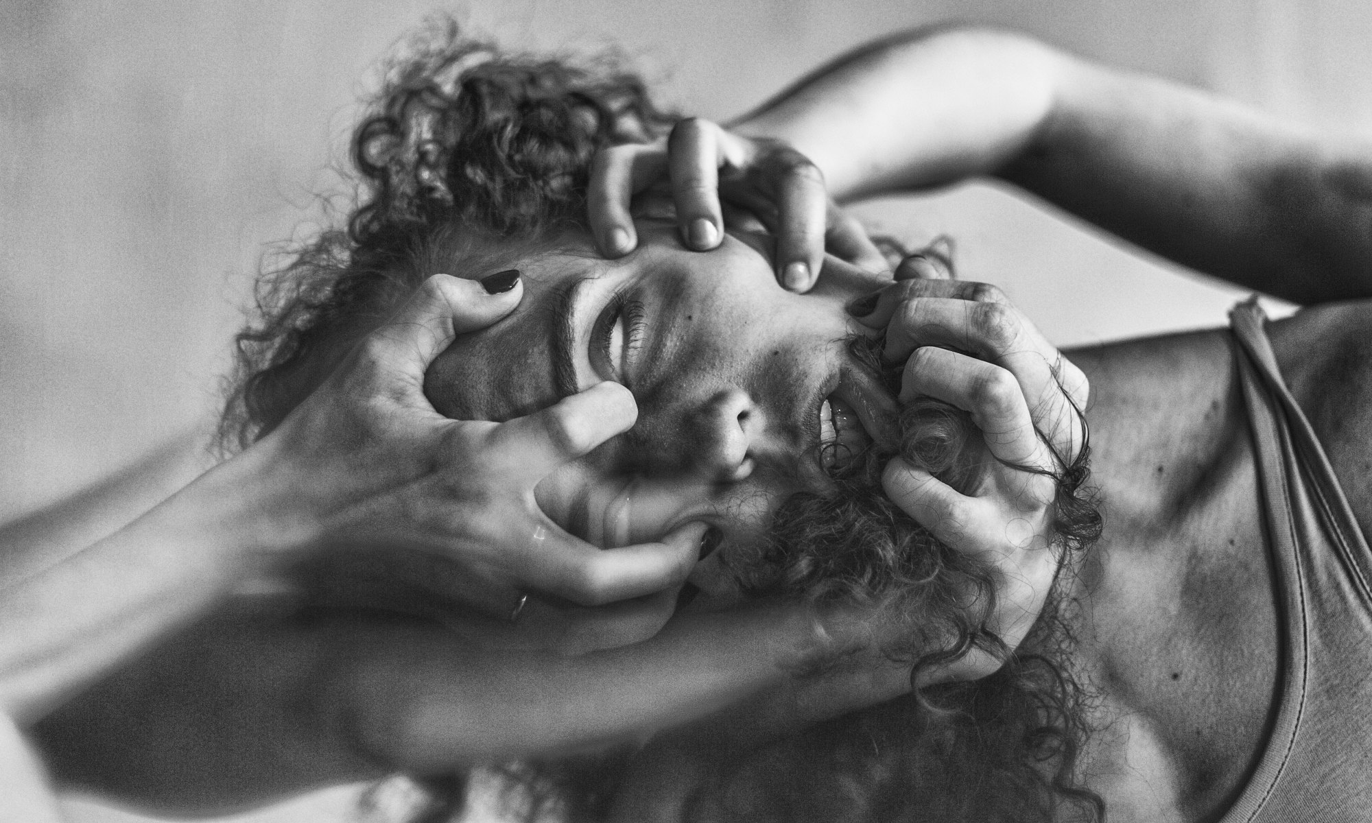 Three hands on man's face experiencing depersonalization disorder