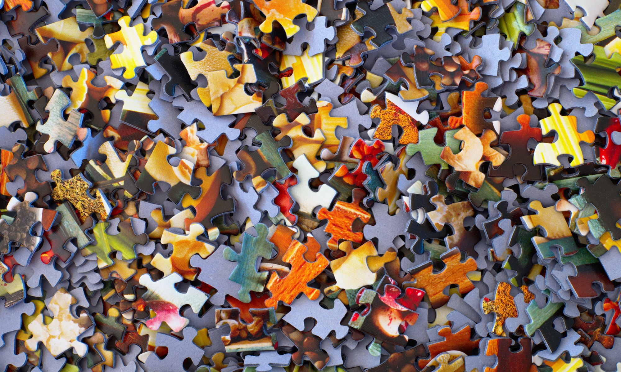 Stack of colorful jigsaw puzzle pieces representing life's problems