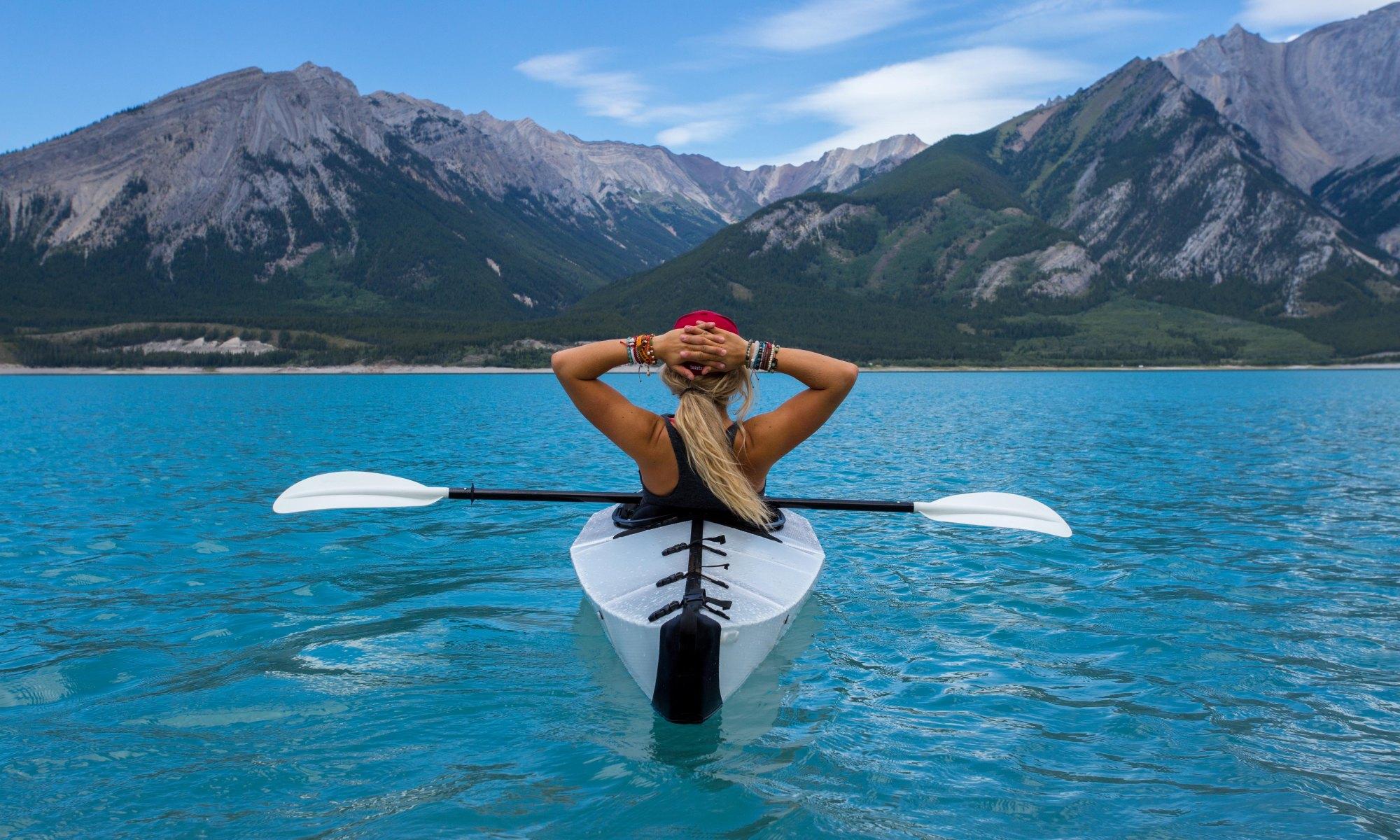 Blonde white woman enjoying solitude riding kayak in blue water