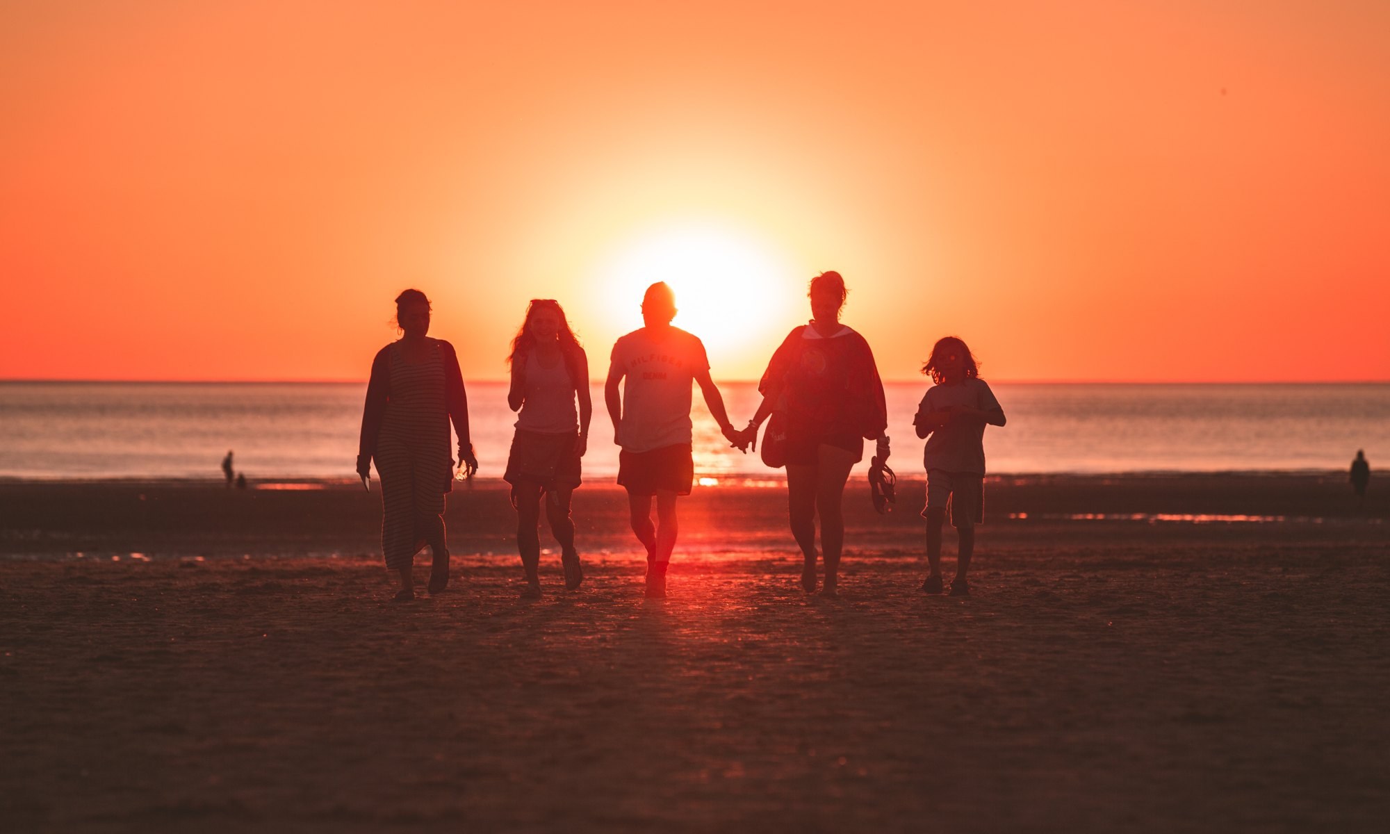 Five person family walking on seashore during golden hour