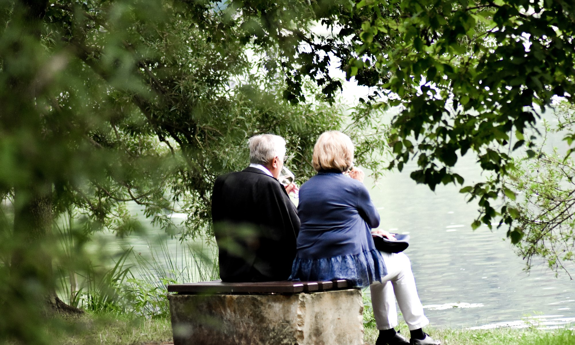 Parents sitting on pavement looking at body of water