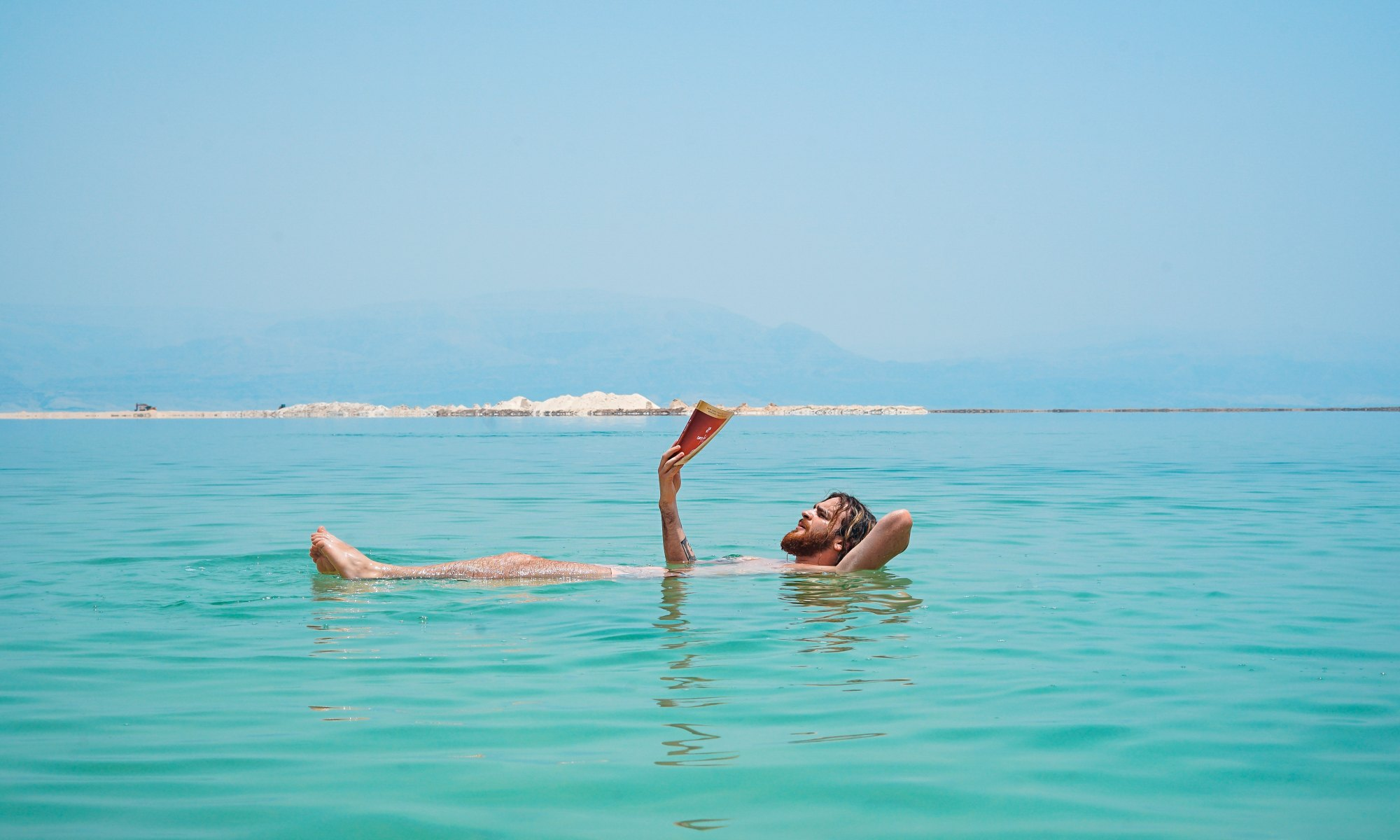 Man floating on turquoise body of water reading a book