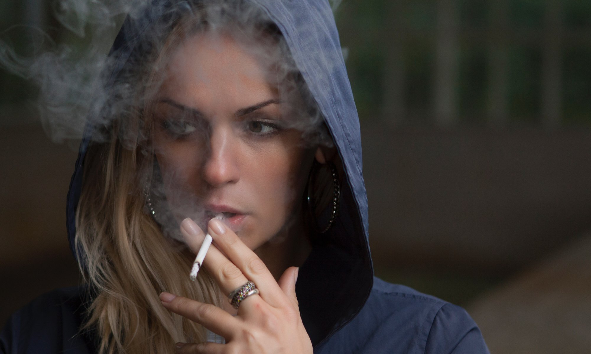 Addicted blonde woman wearing blue hoodie and smoking a cigarette