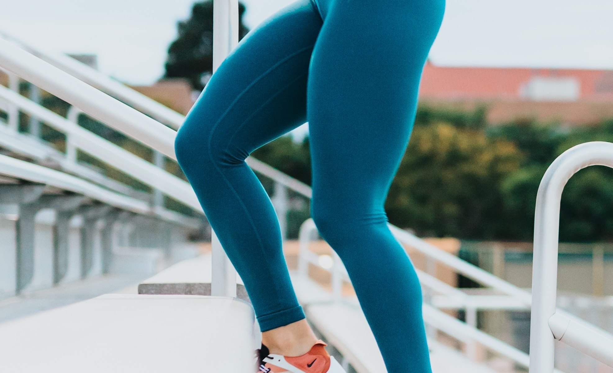 Attractive woman jogging on stadium bleachers in blue spandex