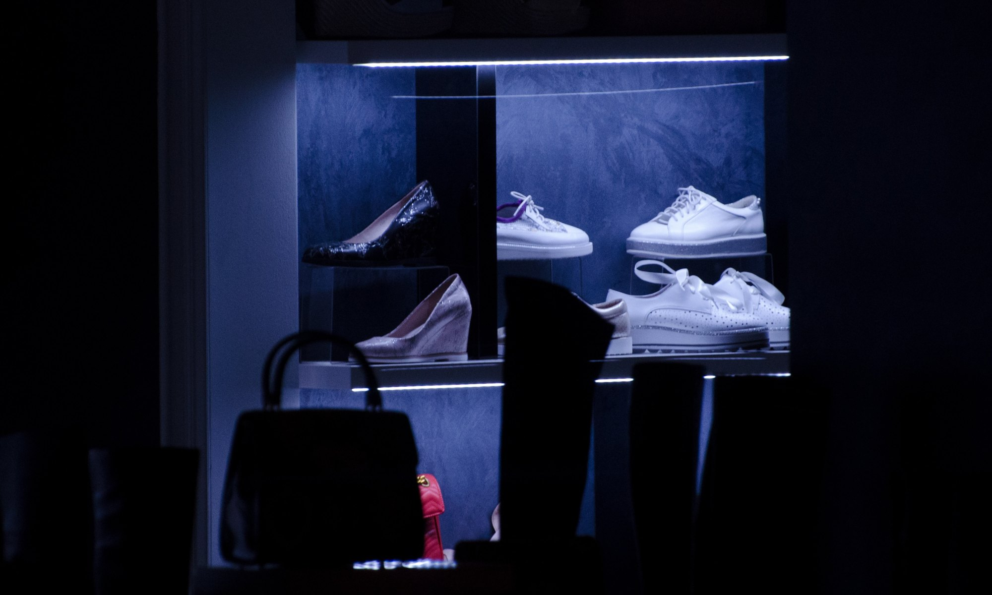 Compulsive buying of shoes and bags in a lit display collection inside a dark room