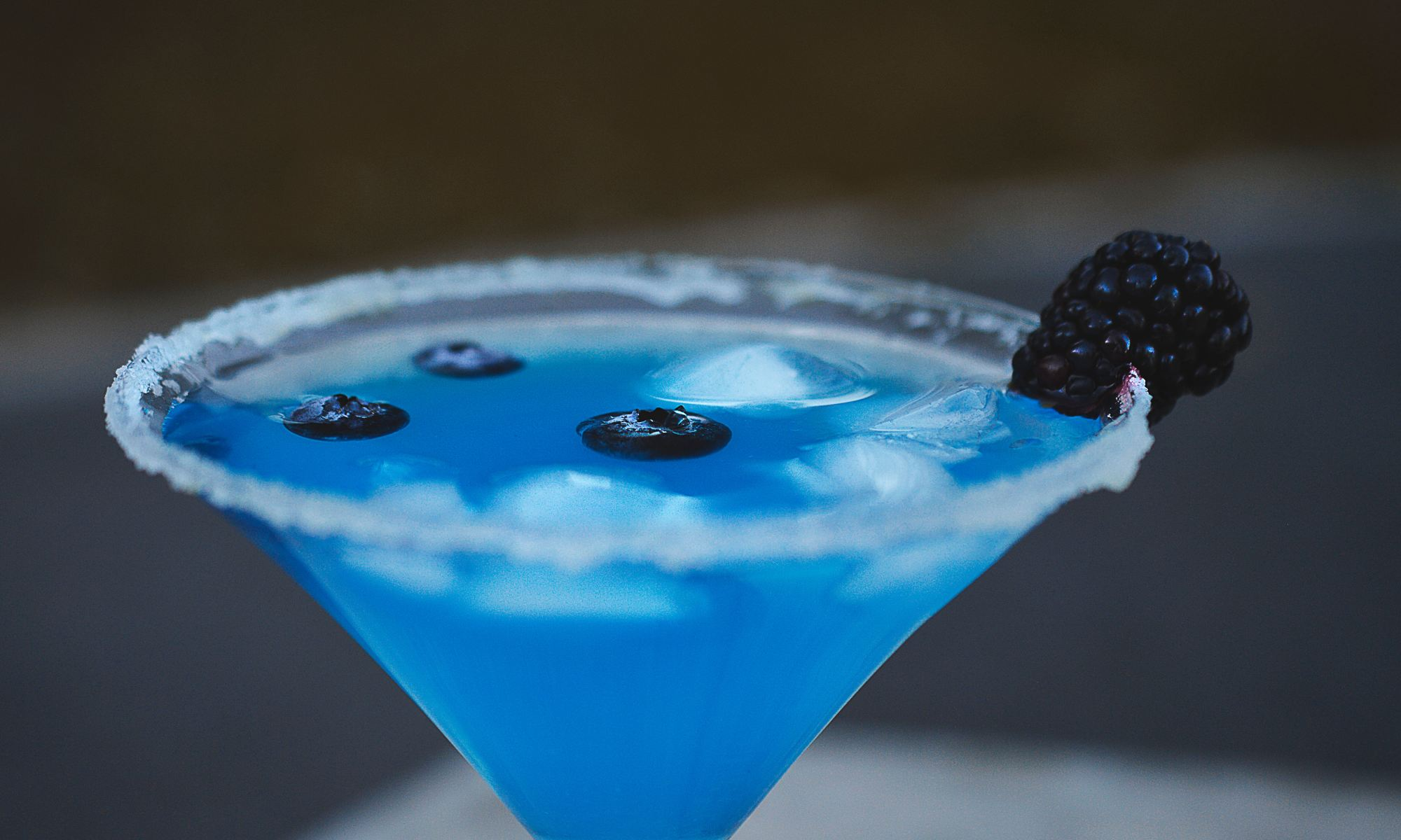 Blue alcoholic drink in martini glass
