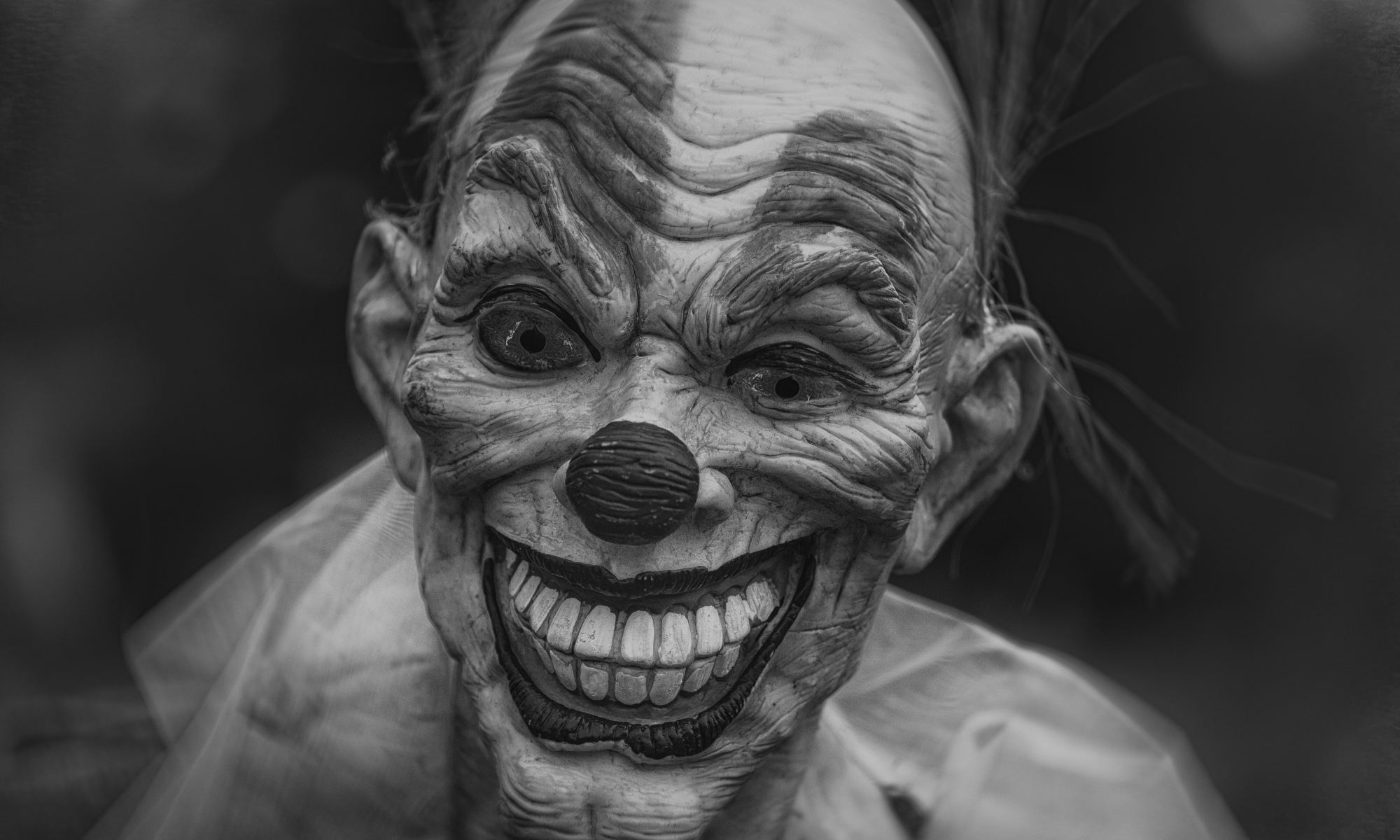 Grayscale photography of annoying person wearing clown mask
