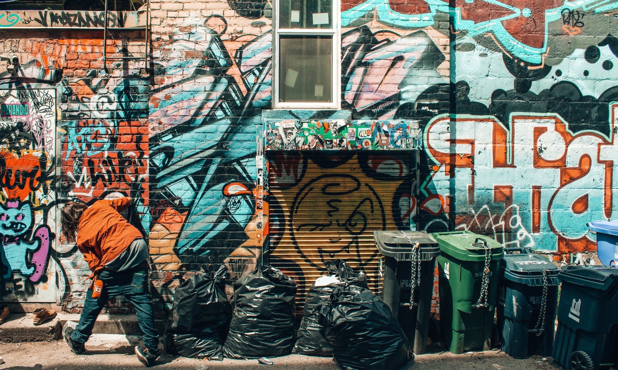 Crystal meth addict standing in front of graffiti wall besides trash bags