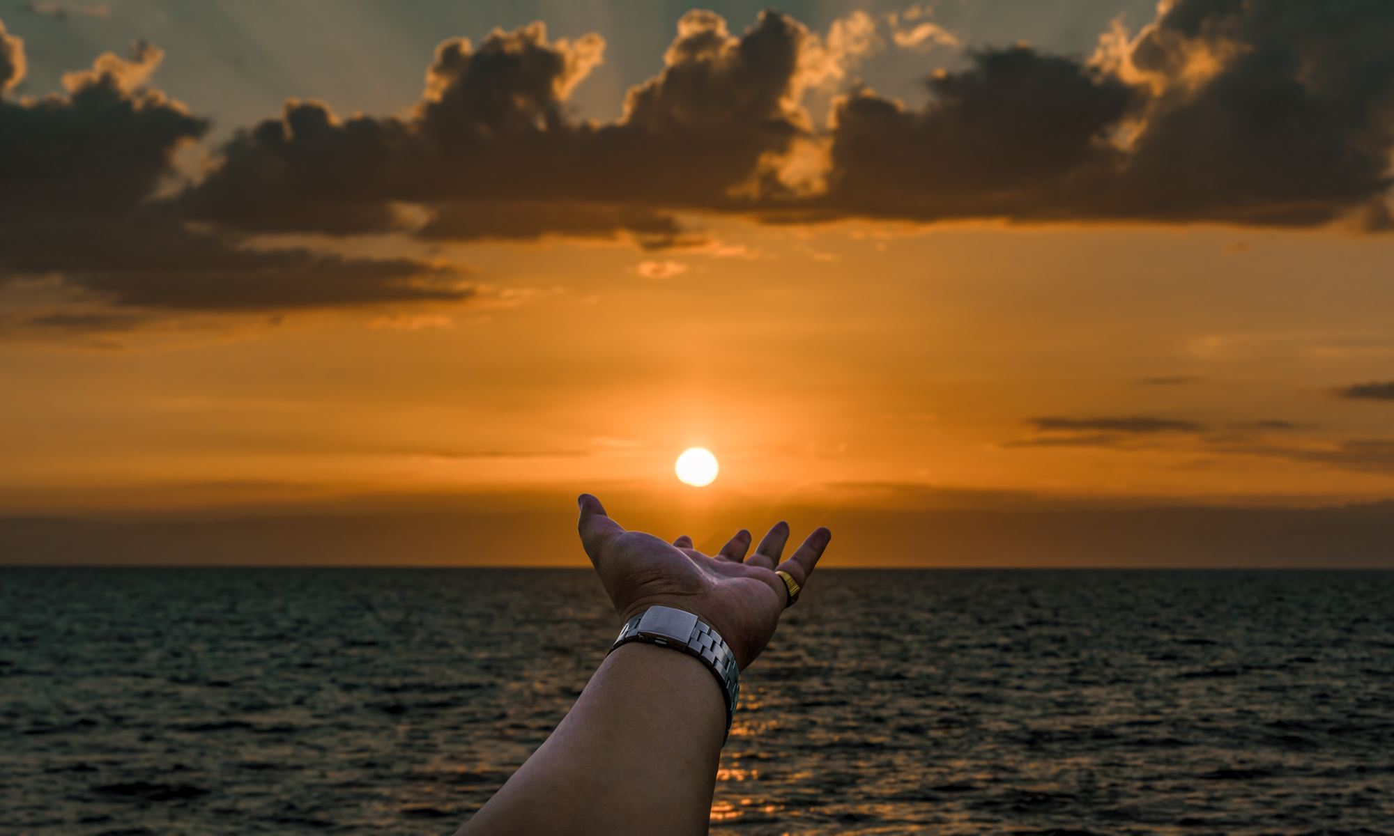 Motivated person extending hand toward ocean during golden hour