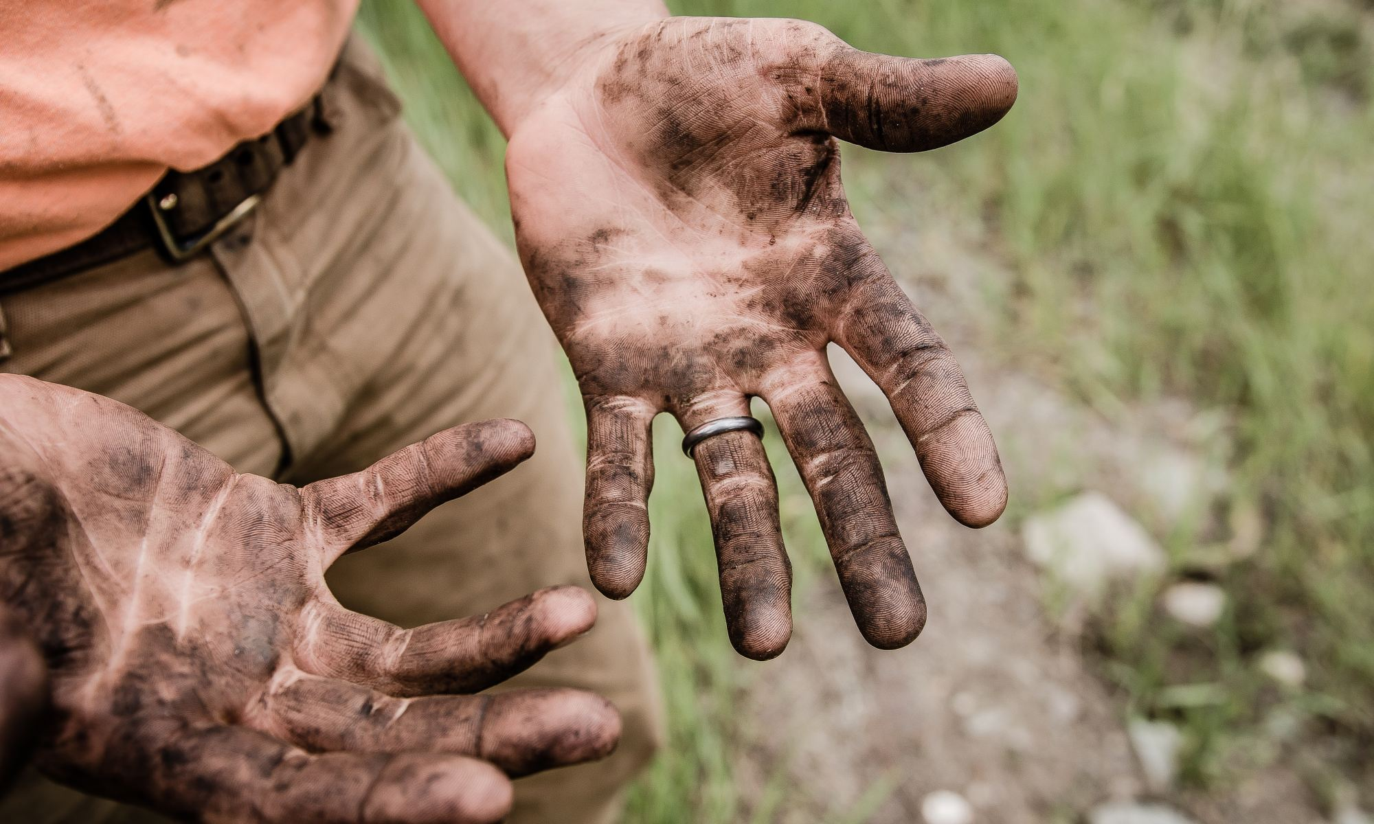 Hard working man with his hands covered in mud