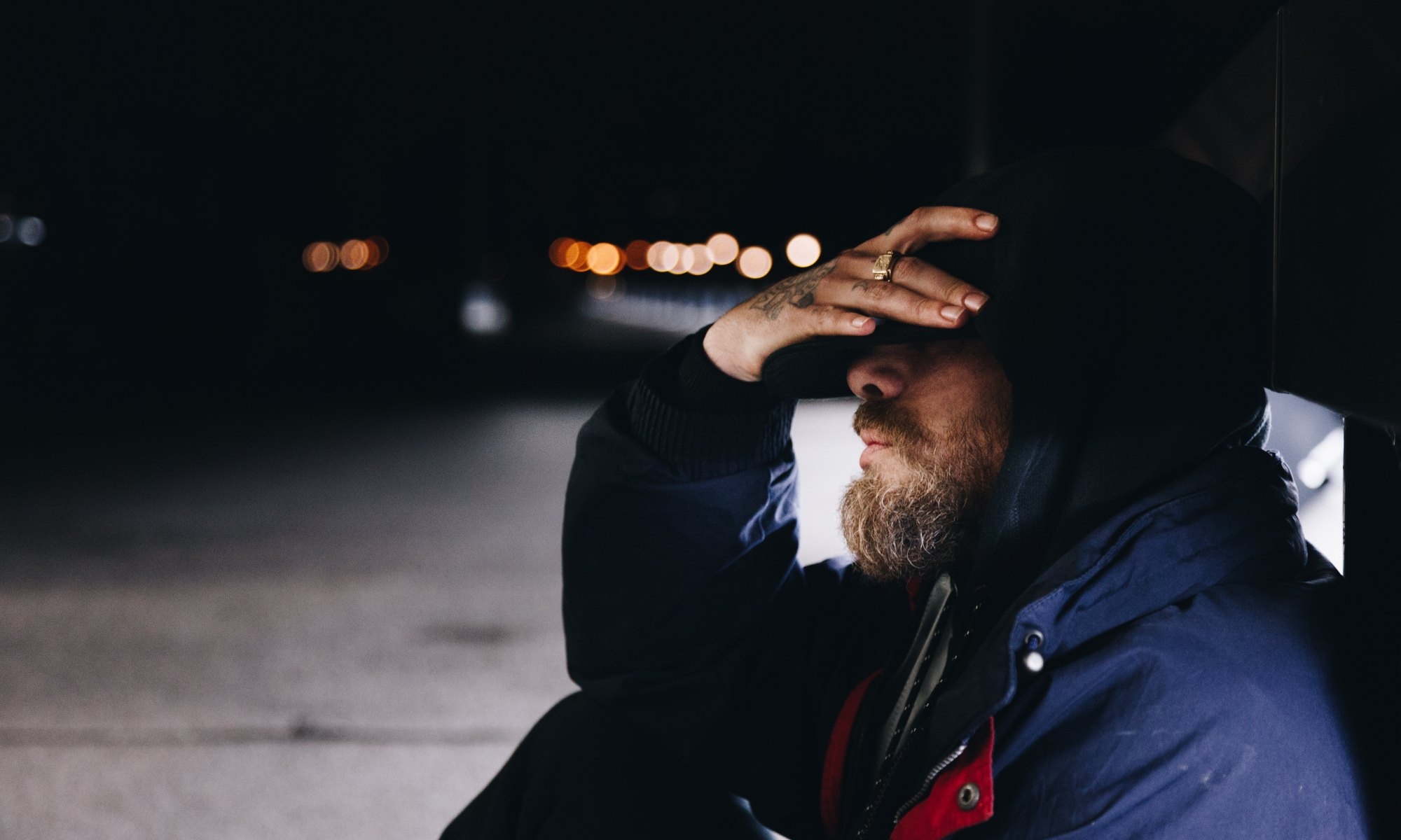 Depressed man sitting on street with hand on face