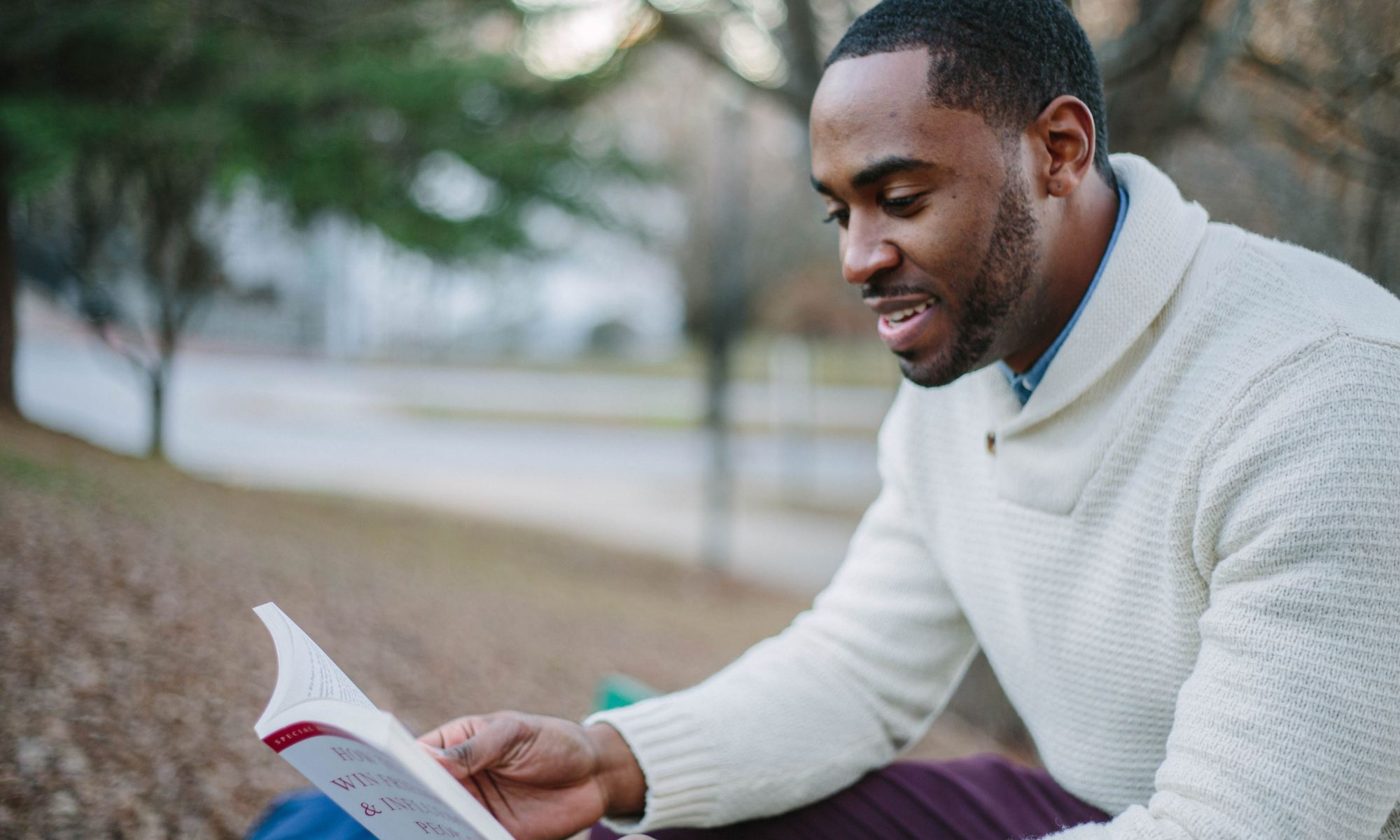 Black man wearing a white sweater while reading a book