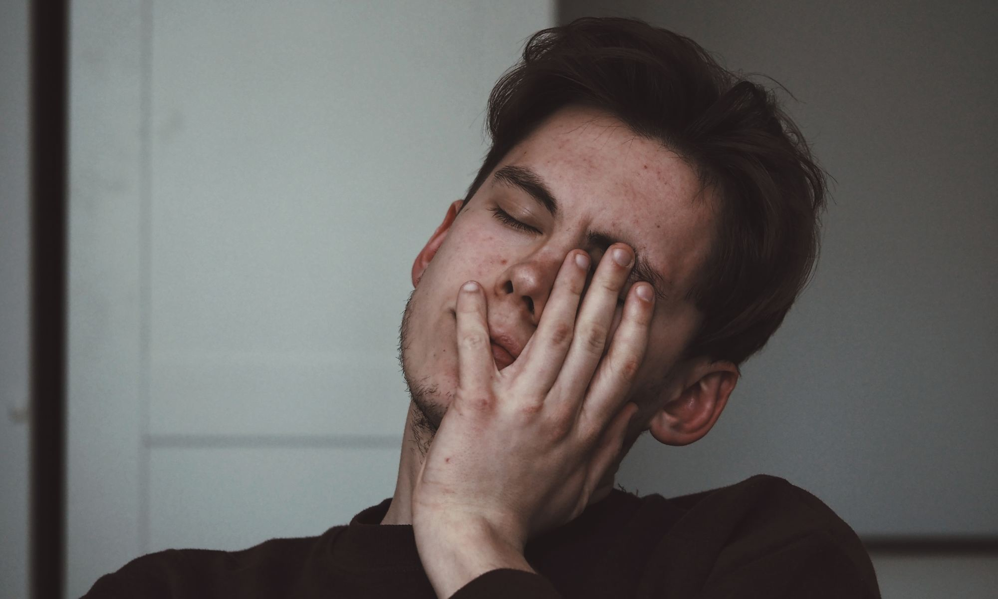 Man with hand on his face suffering from lack of sleep