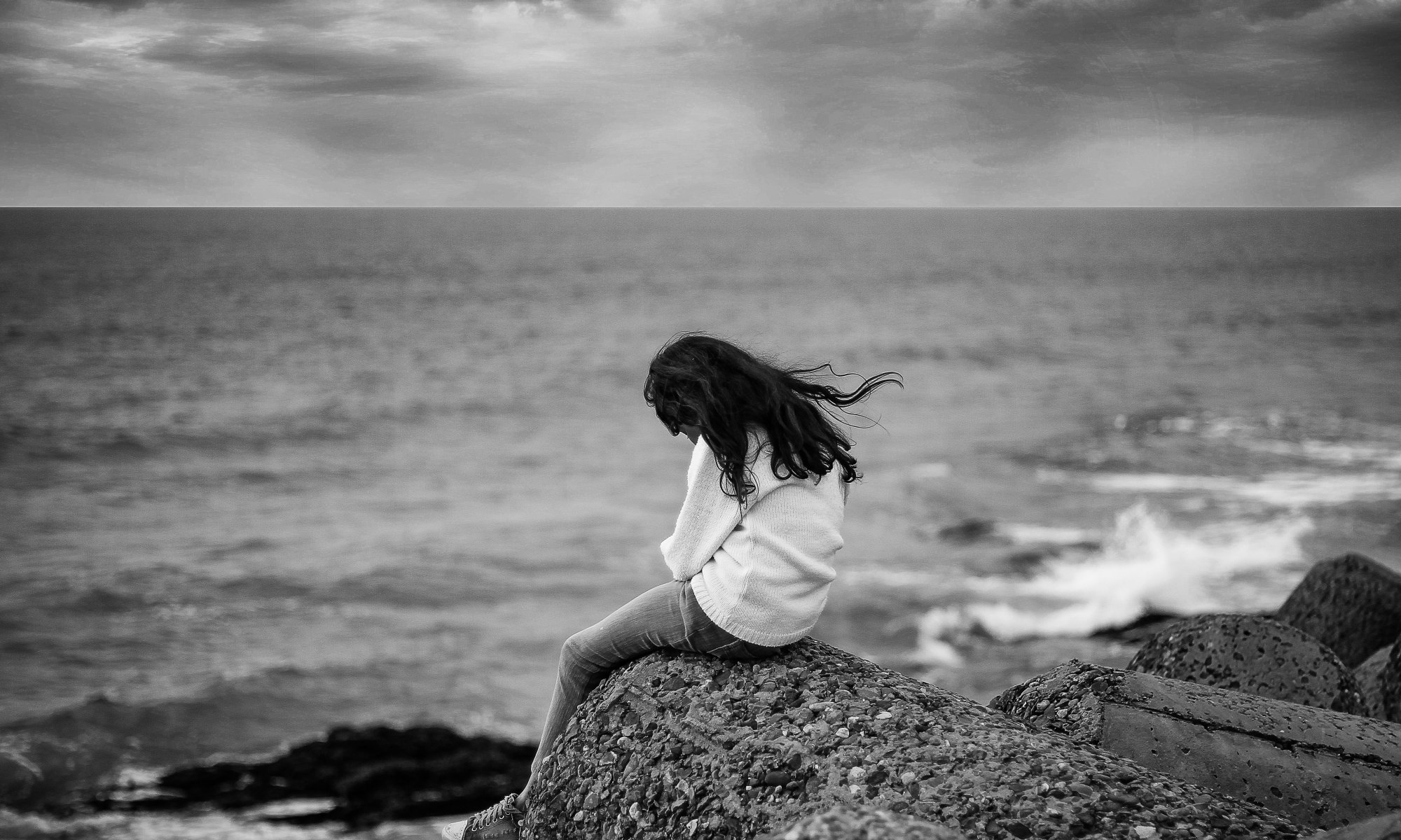 Grayscale photography of lonely woman sitting near ocean