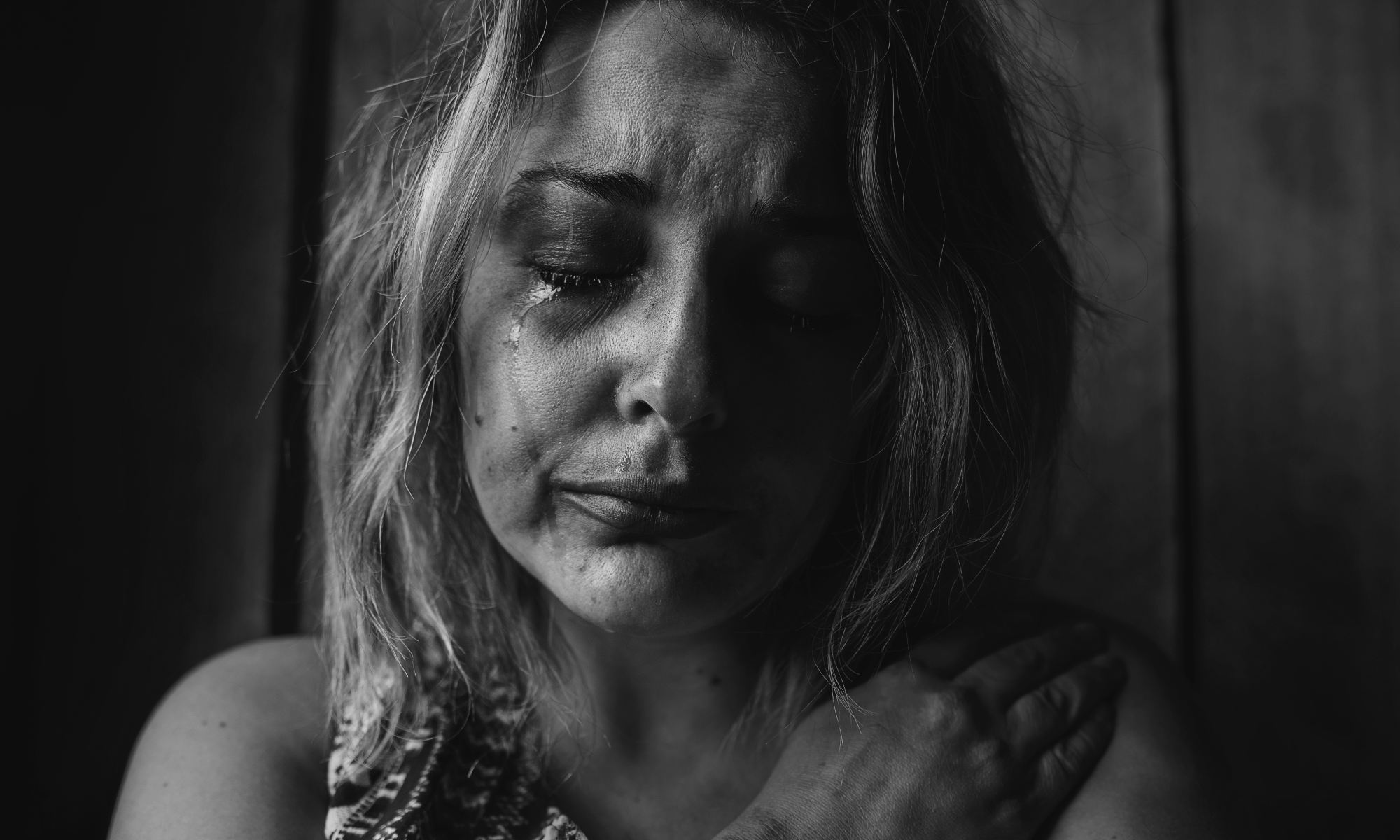 Grayscale photo of a woman crying and suffering from a mental illness