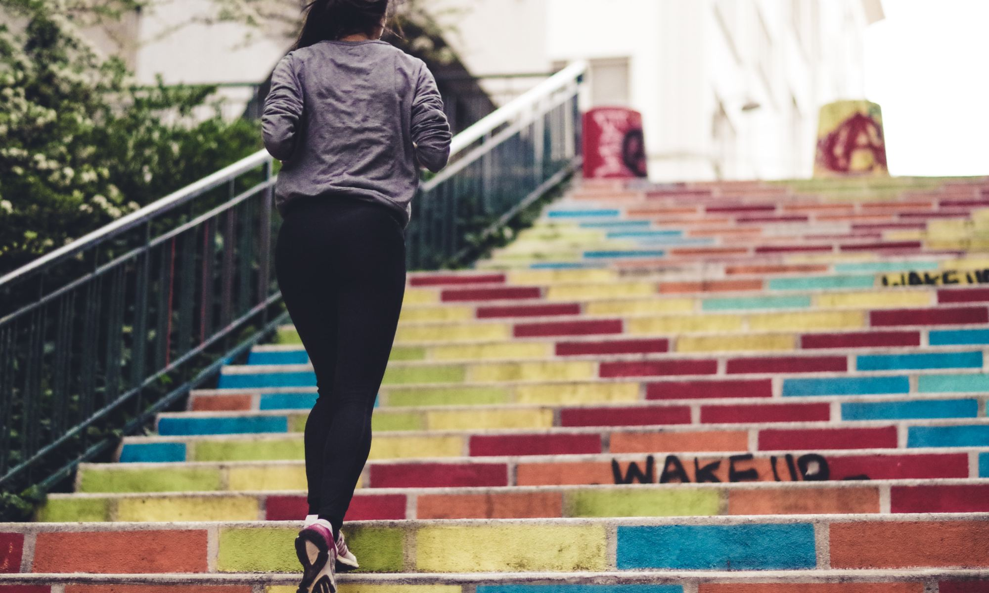 Motivated woman working out by running up the stairs outside