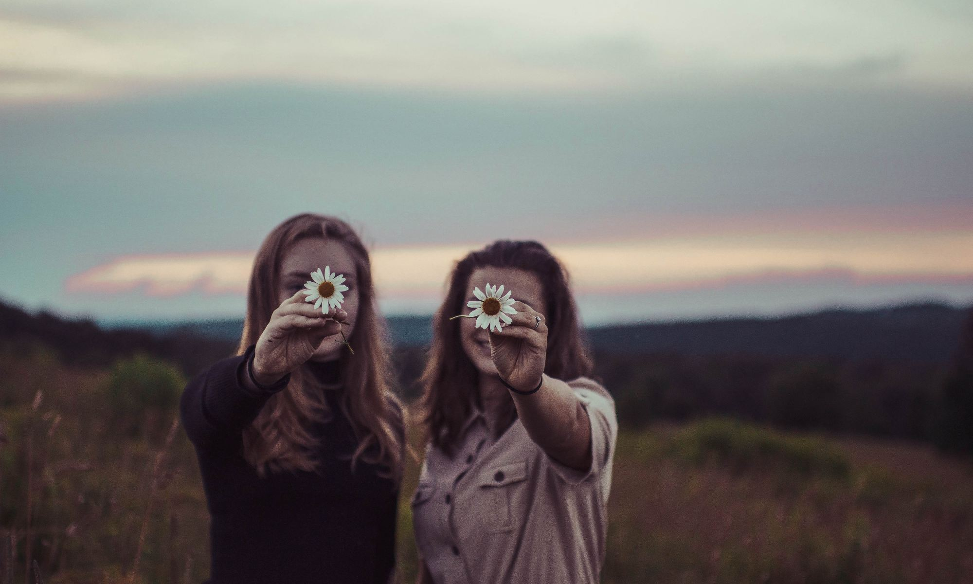 Two female friends holding flowers and reuniting in nature