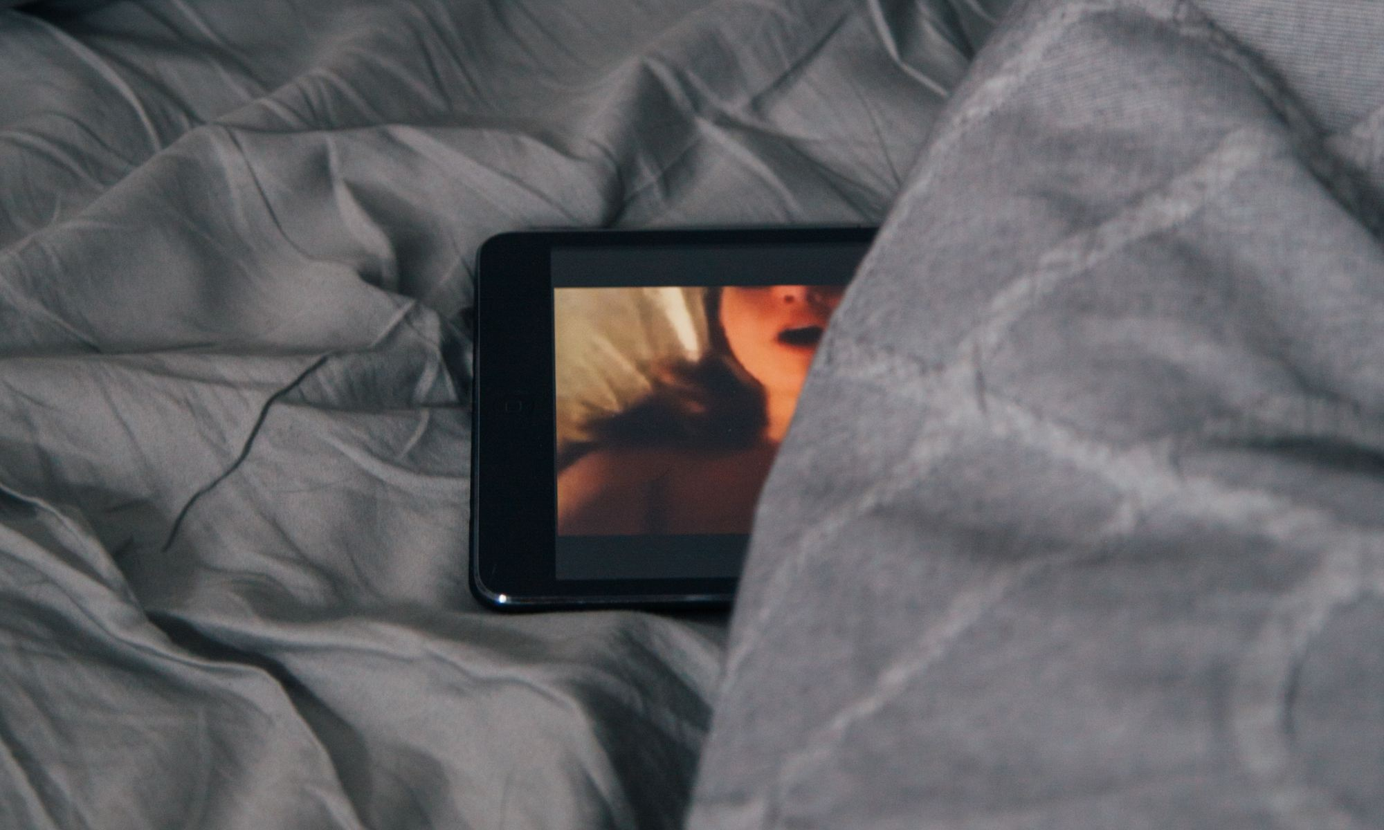Porn playing on black Android smartphone on gray bed sheet