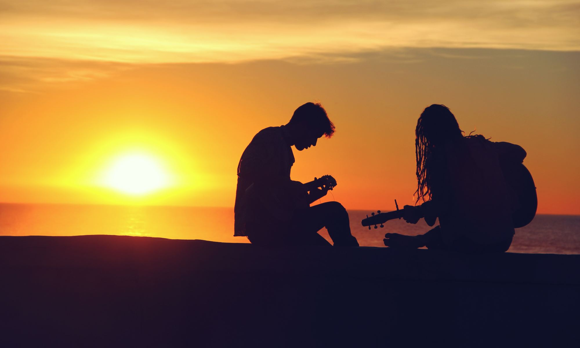 Silhouette of man and woman playing guitars and enjoying music