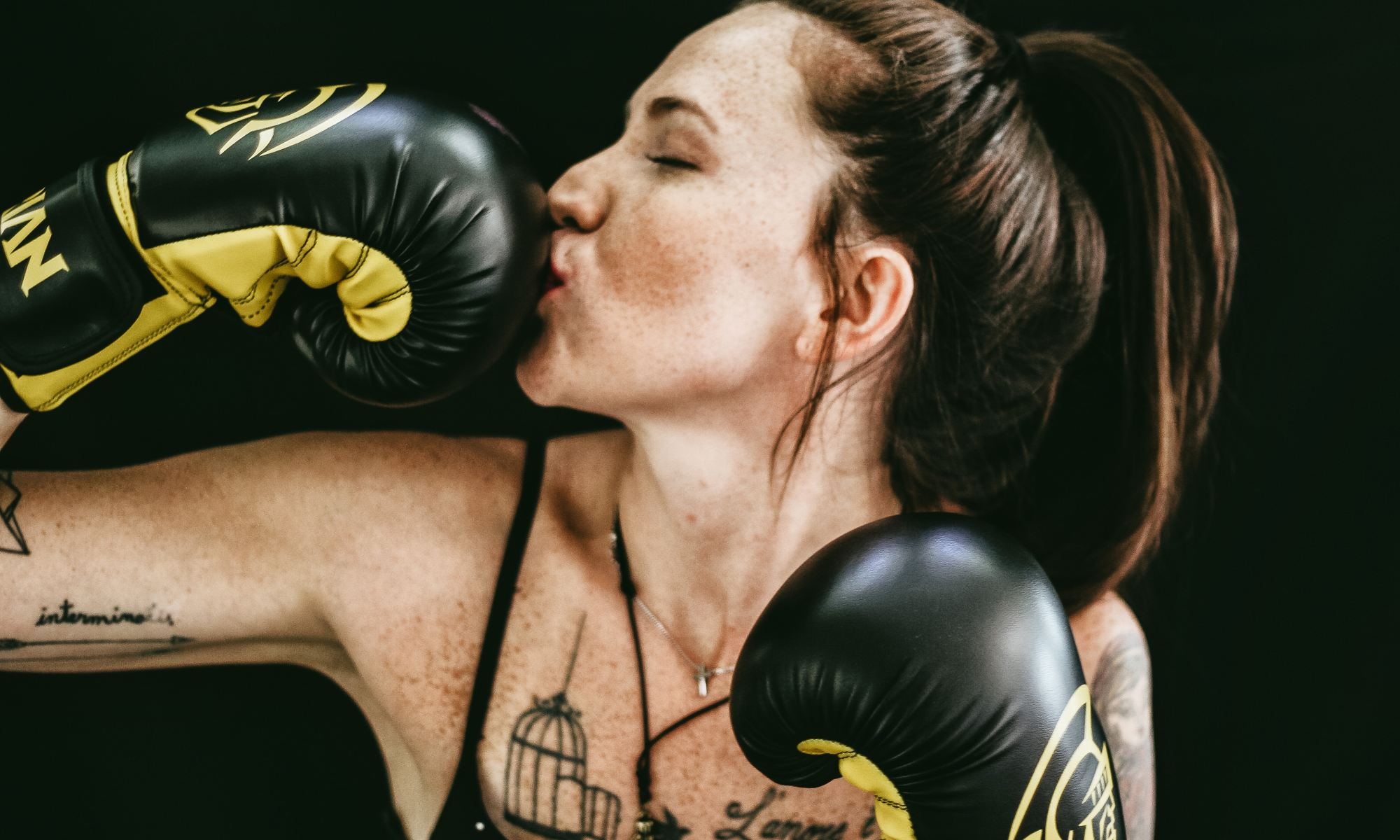 Successful woman with strong beliefs kissing black leather boxing gloves