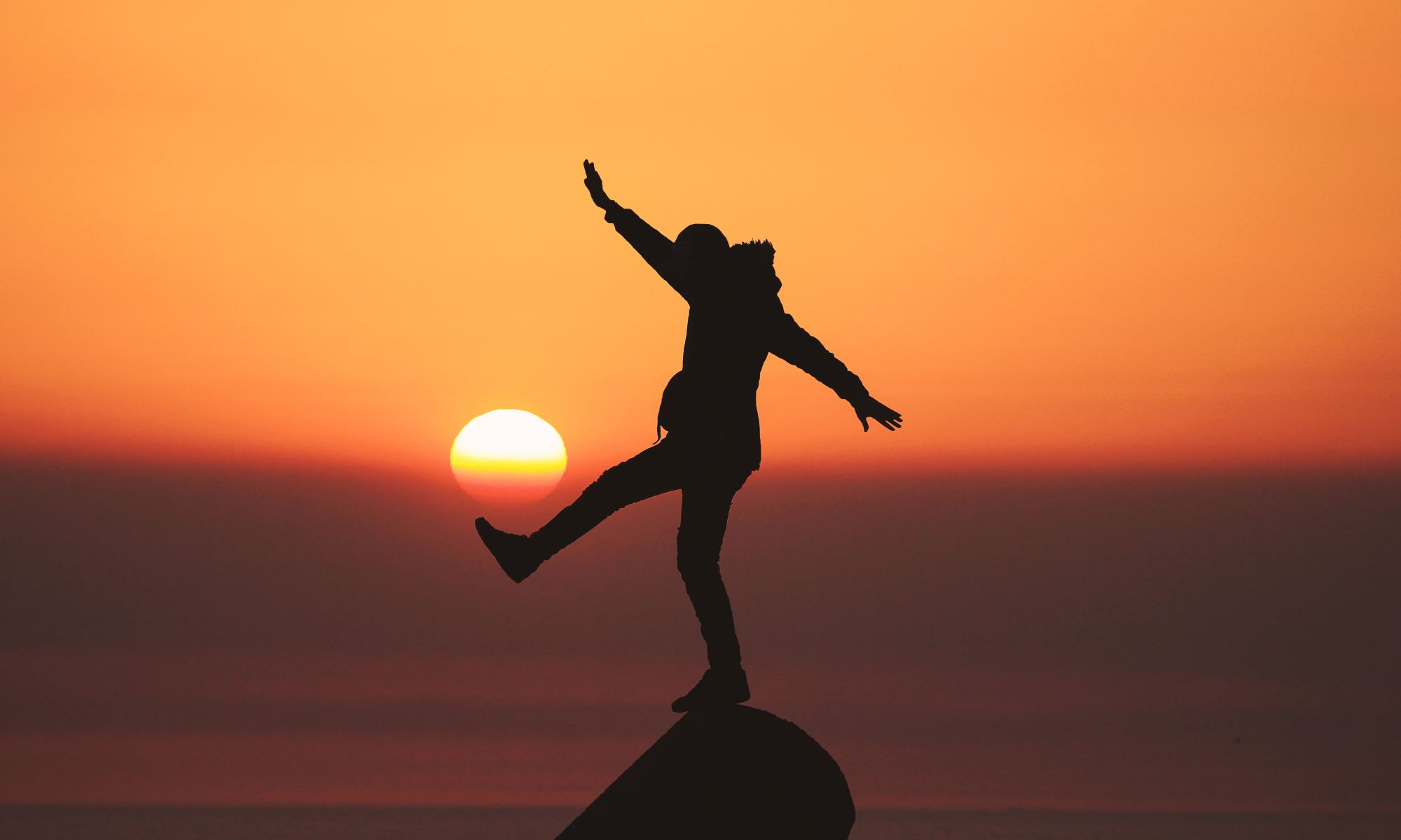 Silhouette photo of man standing on a rock practicing work-life balance
