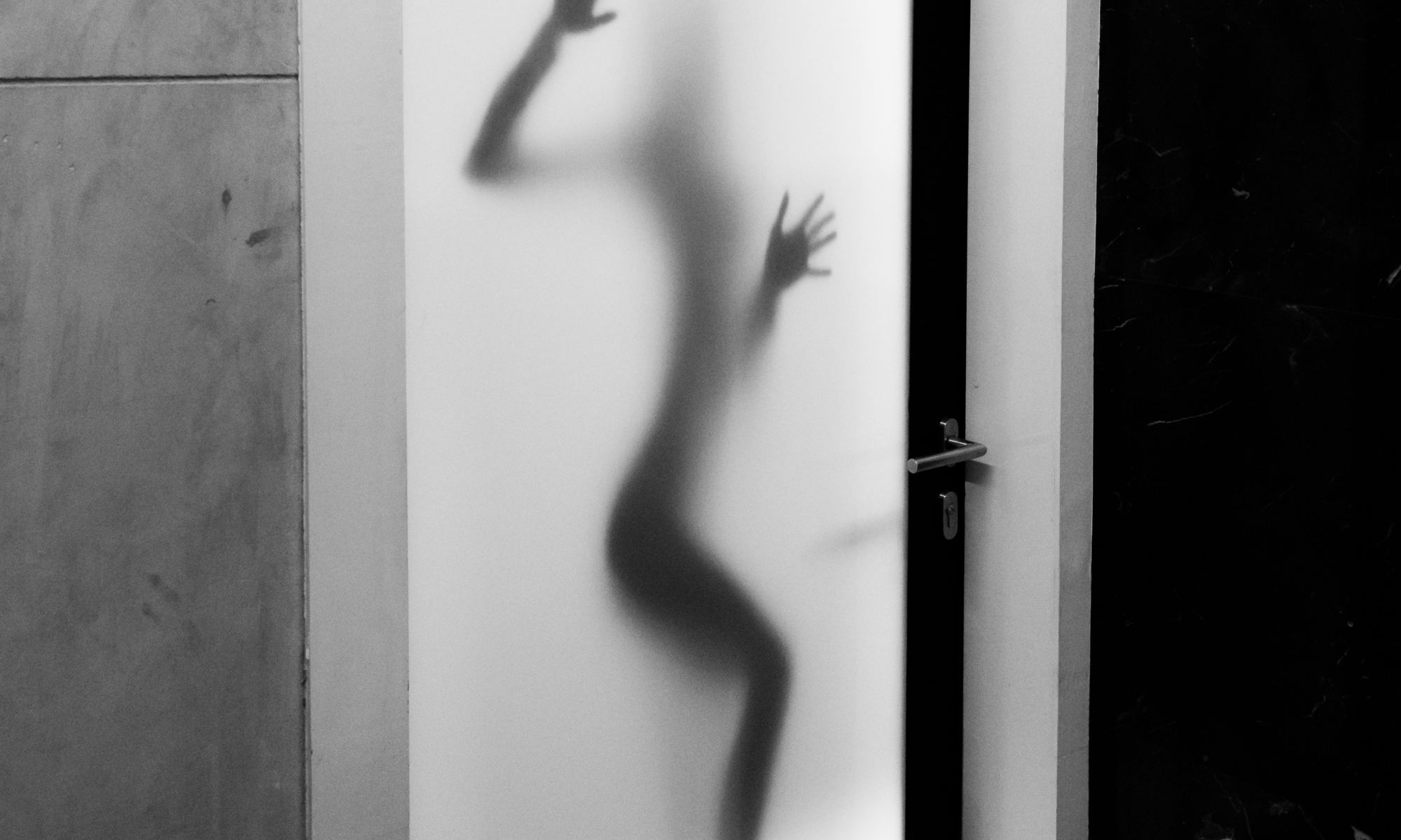 Shadow of person with body dysmorphic disorder against white panel glass door