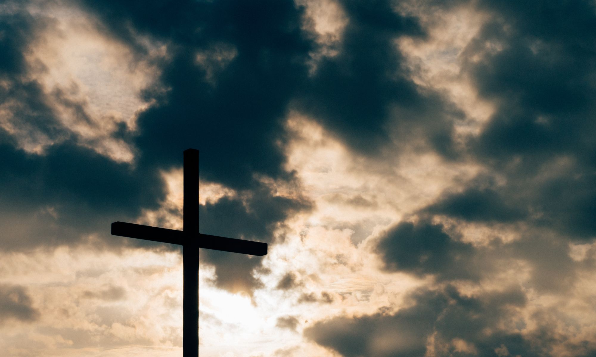 Silhouette of cross under dark clouds