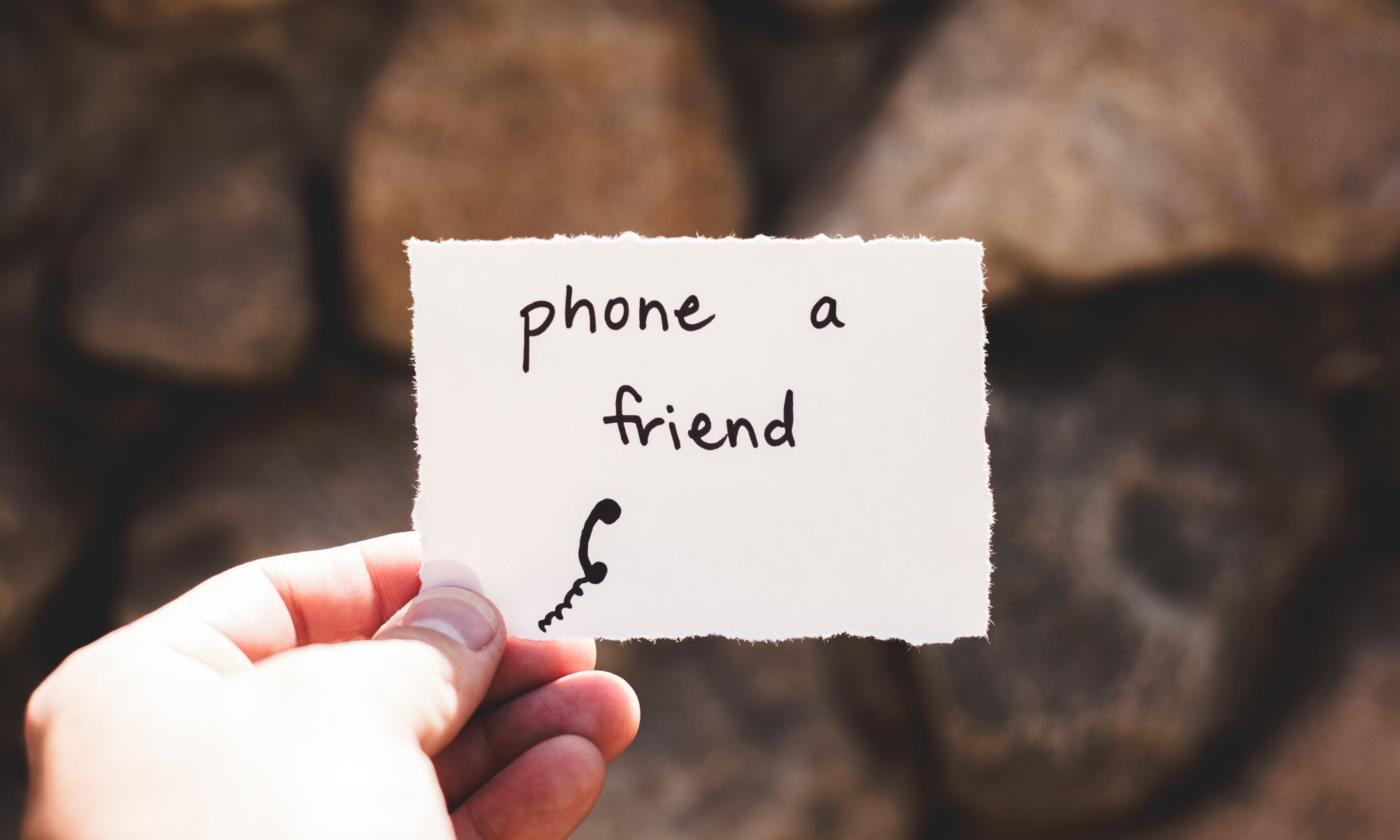 "Person holding a piece of paper with ""phone a friend"" written on it"