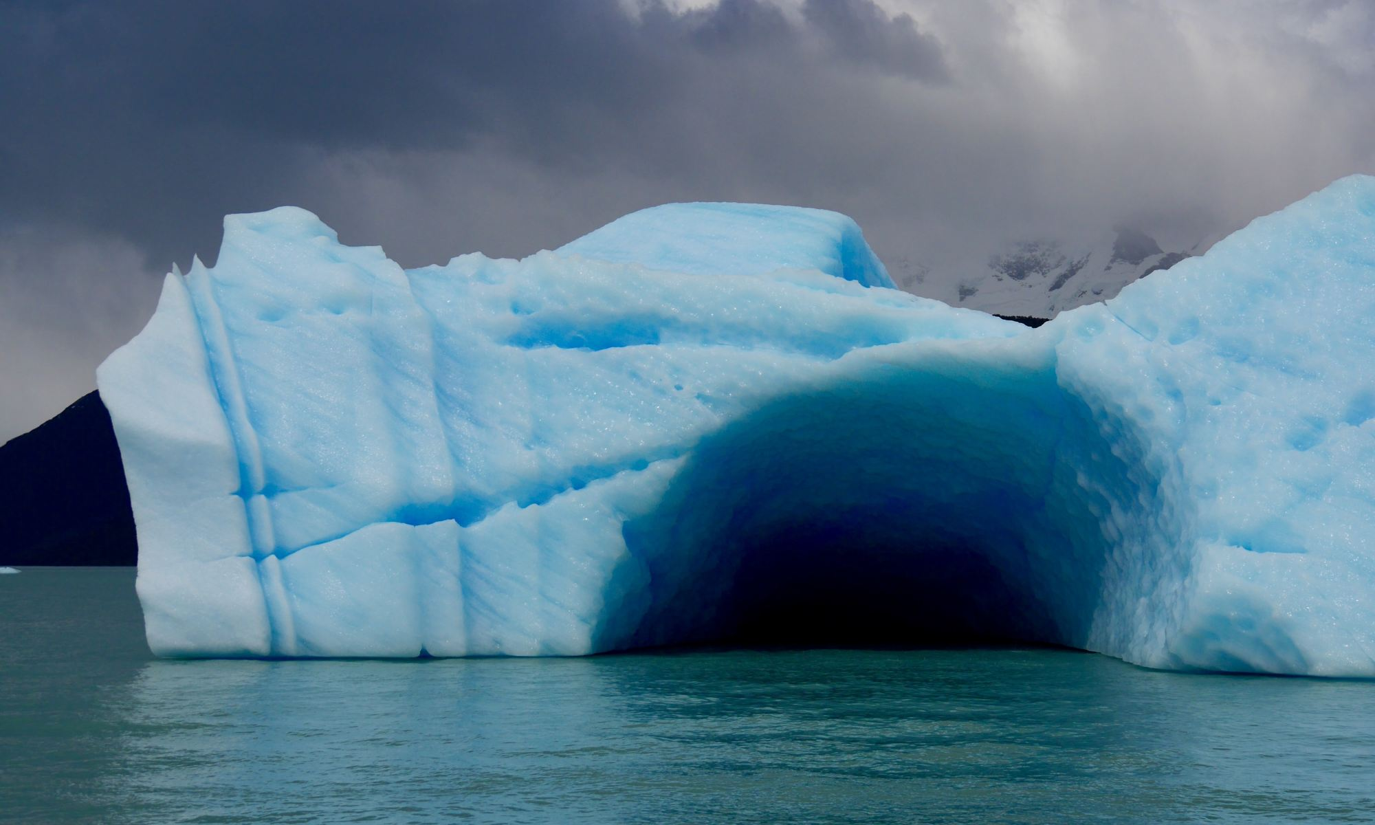 Blue ice cave in the middle of an iceberg floating on body of water