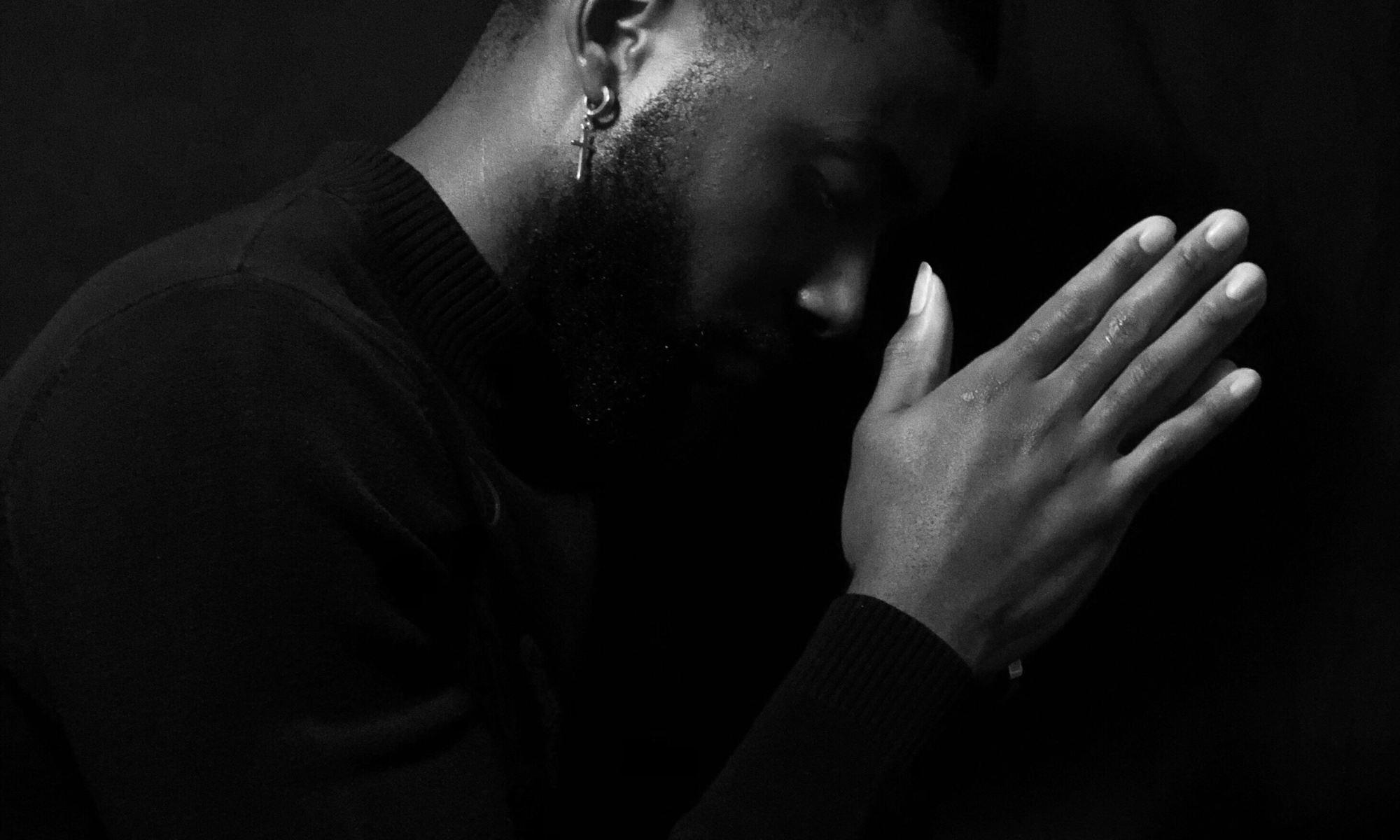 Young black male with mental illness praying