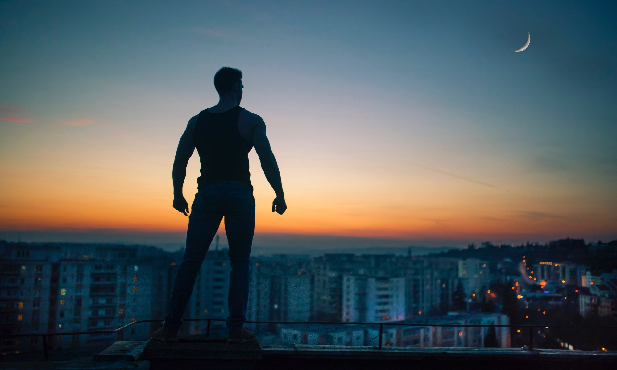 Silhouette photography of man standing on roof of building demonstrating persistence