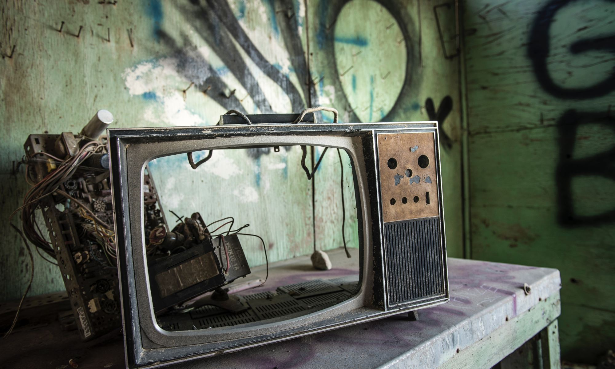 Broken vintage television on wooden table in front of graffiti-sprayed walls