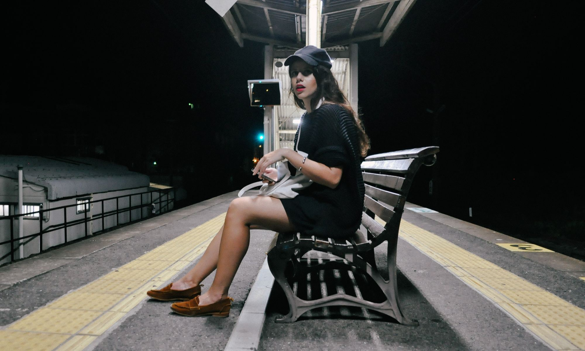 Single brunette woman sitting on bench waiting for metro