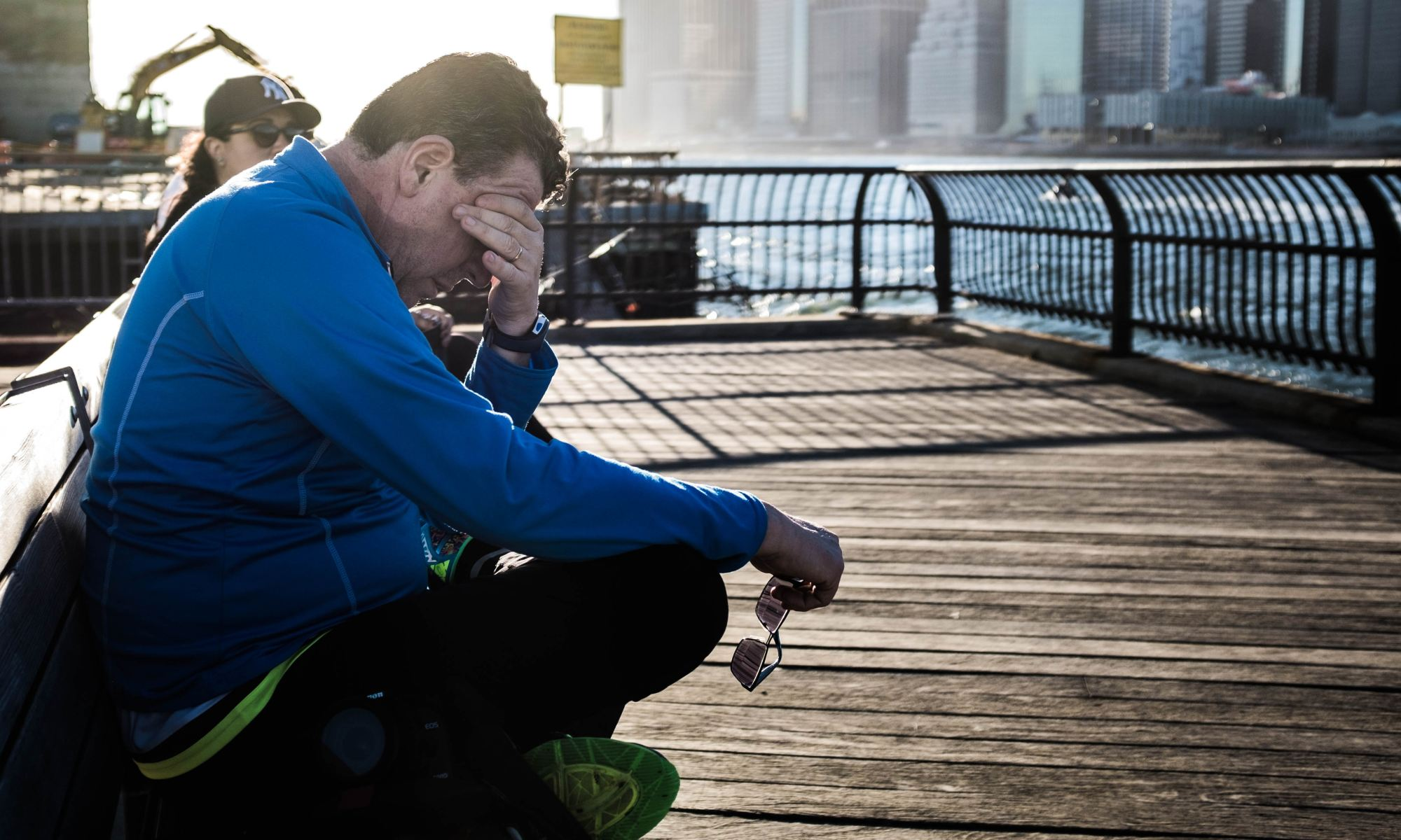 Fatigued man sitting on bench besides body of water