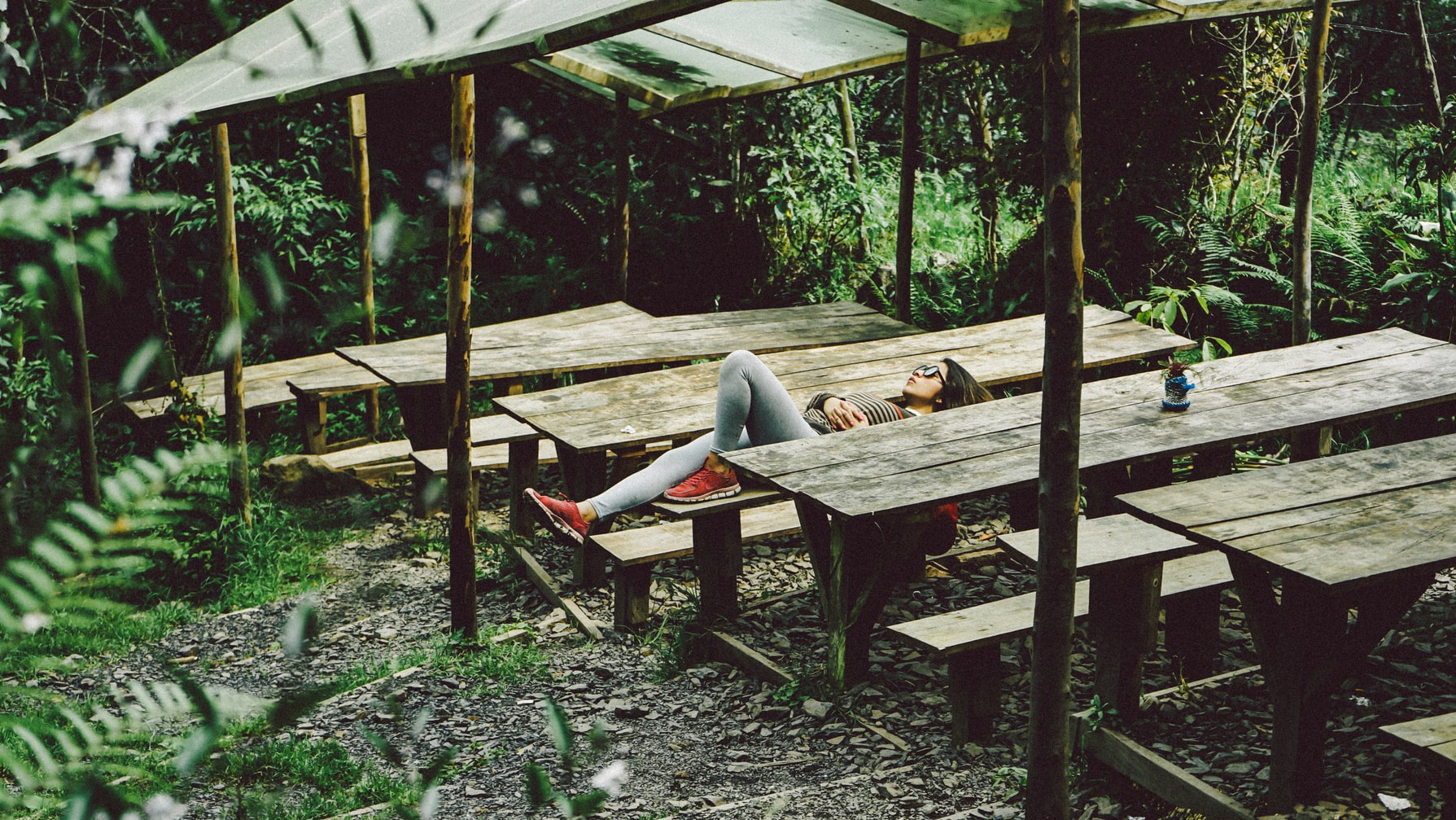 Woman taking a break from work and lying on brown wooden picnic table near shrubs