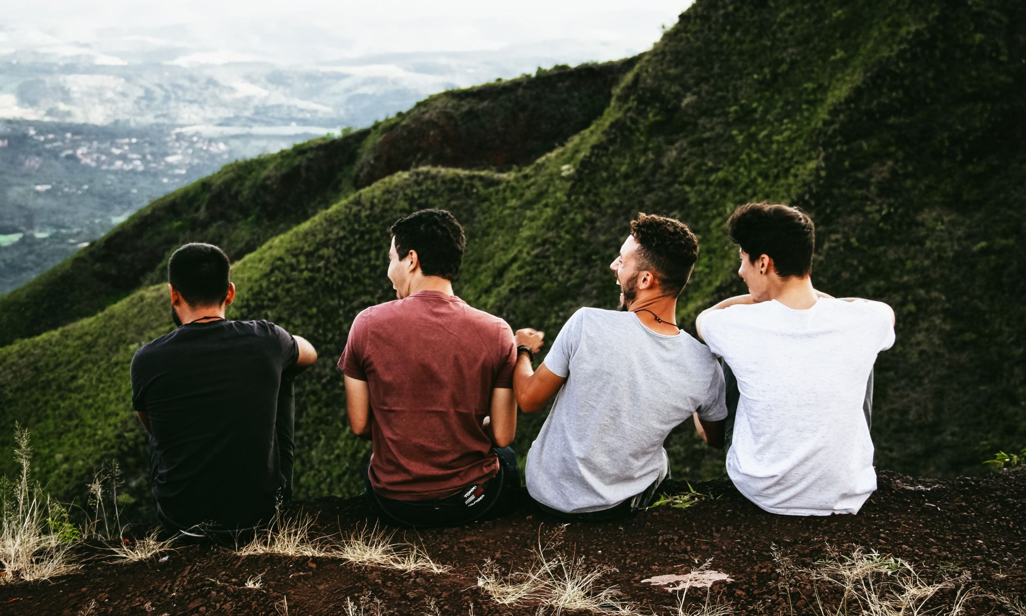 Four teenage boys sitting on mountain trail