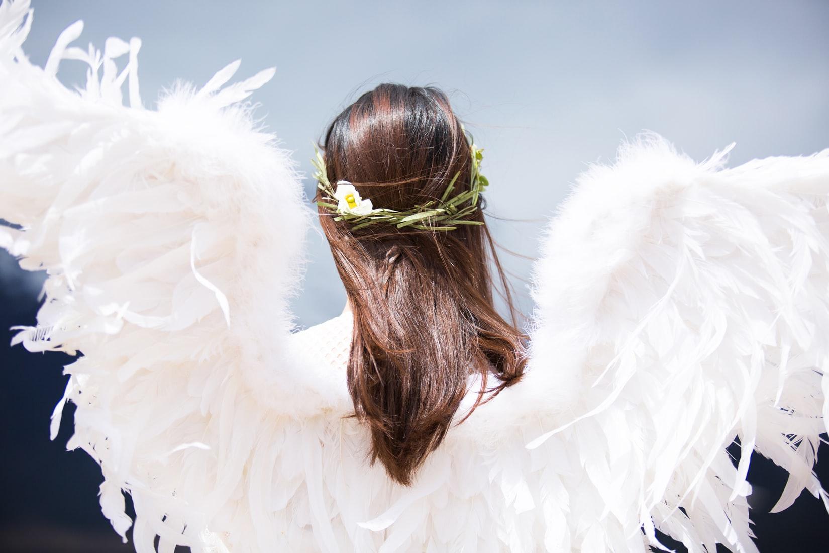 Brunette woman wearing white angel wings