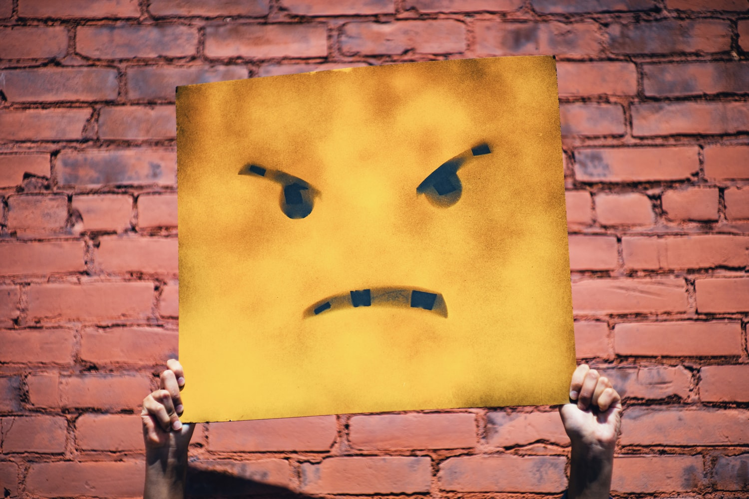 Hands holding yellow angry face illustration in front of brick wall