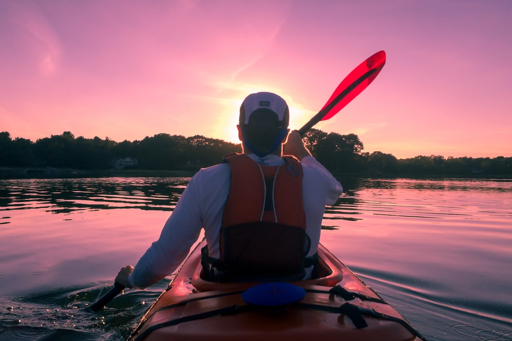 Single man riding on kayak on lake during sunset