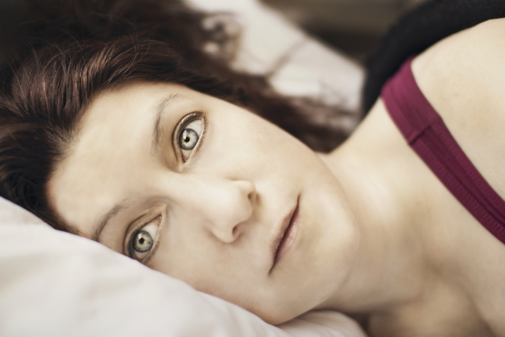 Brunette woman with hazel eyes awake in bed at night due to too many thoughts