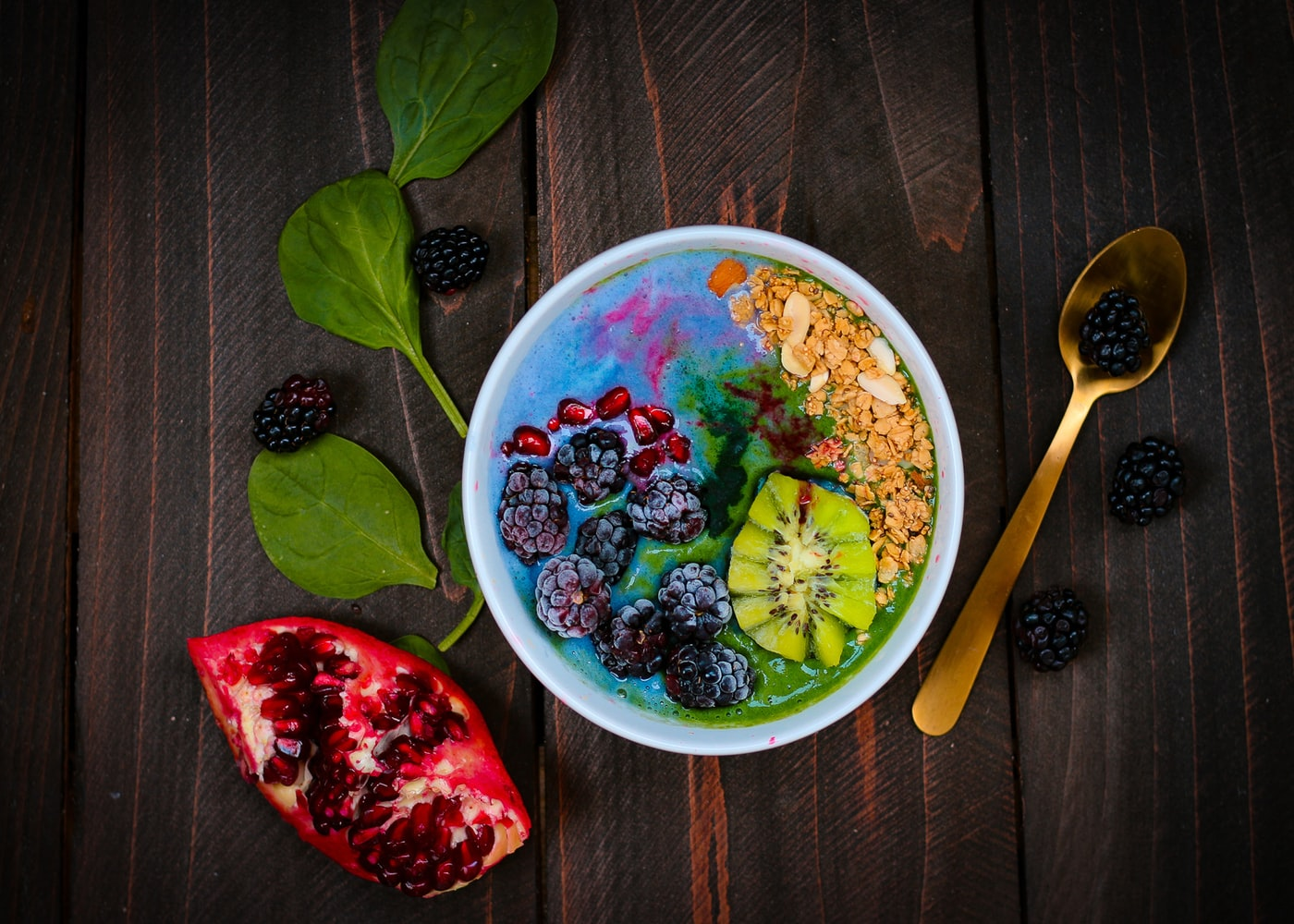 Bowl on wooden table filled with colorful mixed fruits