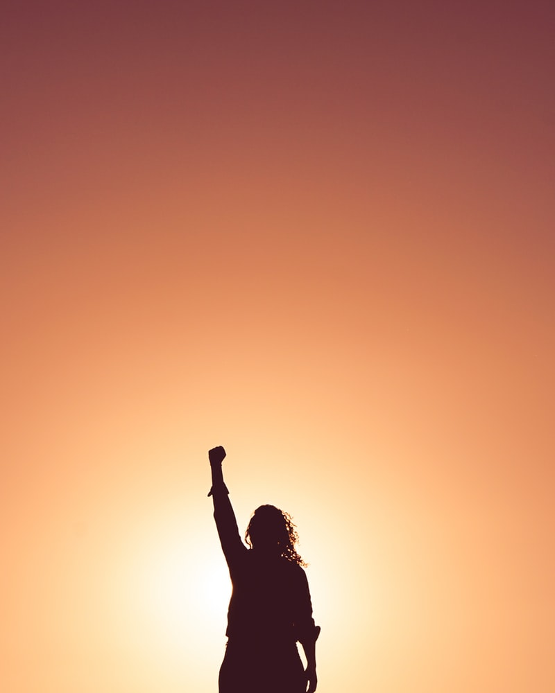 Silhouette of proud woman holding her first in the air