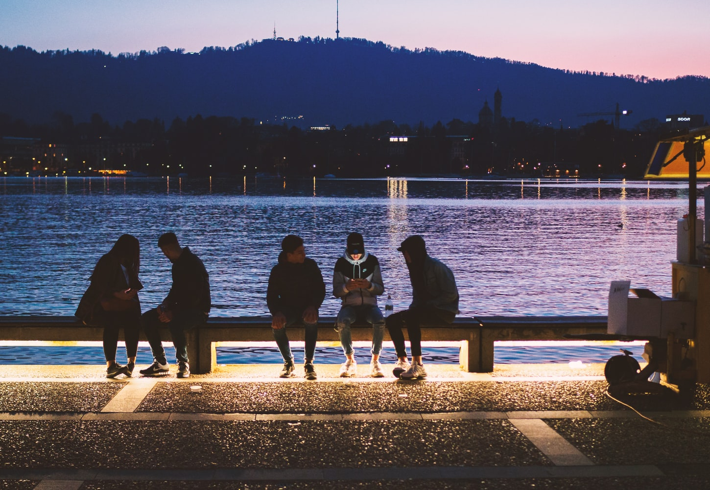 Five millennials sitting near body of water on their cell phones