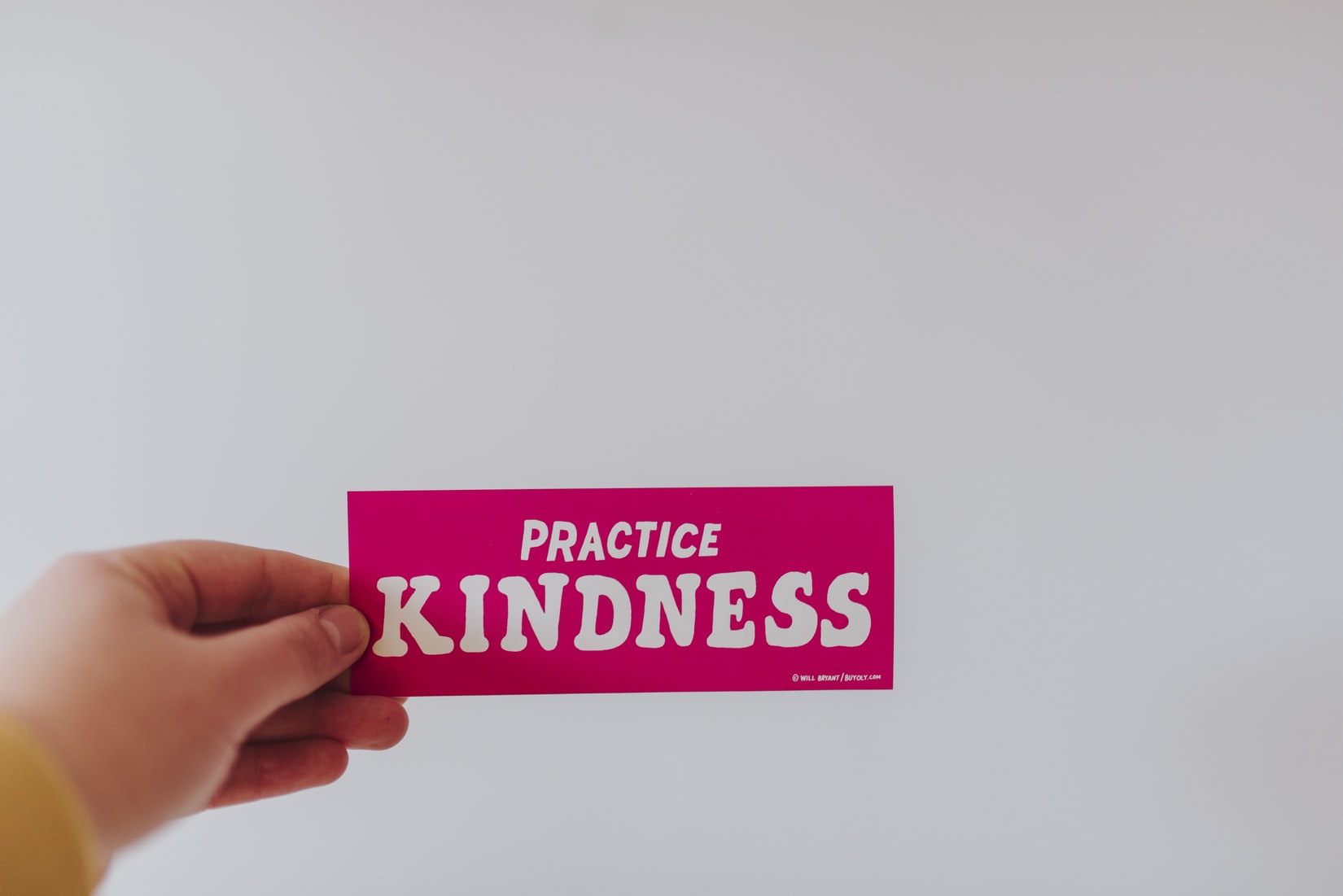 "Hand holding red and white ""practice kindness"" sticker"